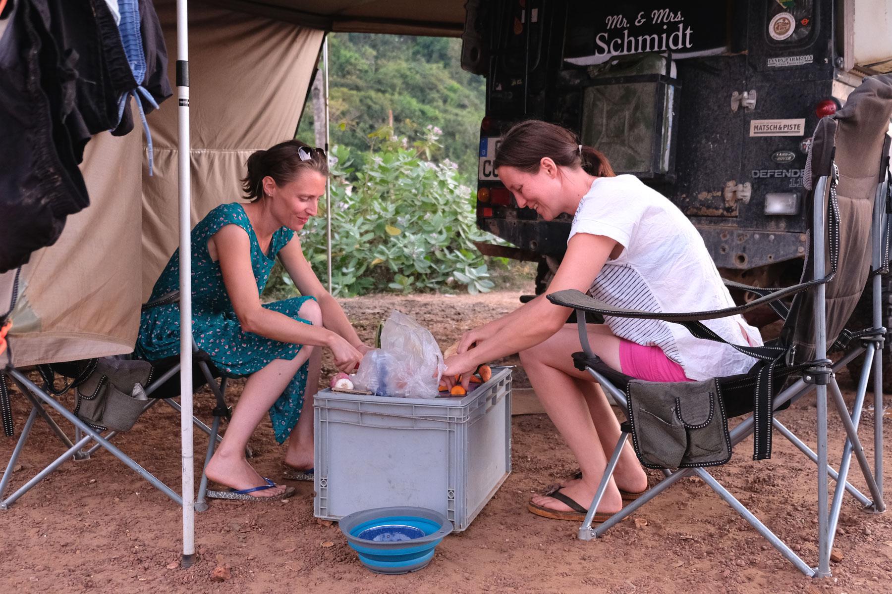 Leo sitzt mit Claudia auf Campingstühlen und schneidet Gemüse.