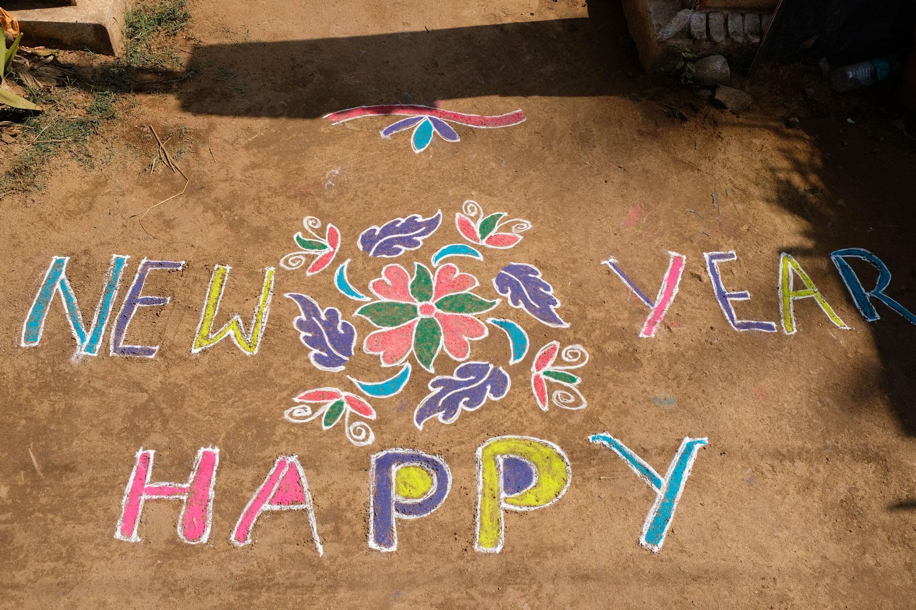 """Mit bunten Farben wurden die Worte """"Happy new year"""" auf den Boden gemalt."""