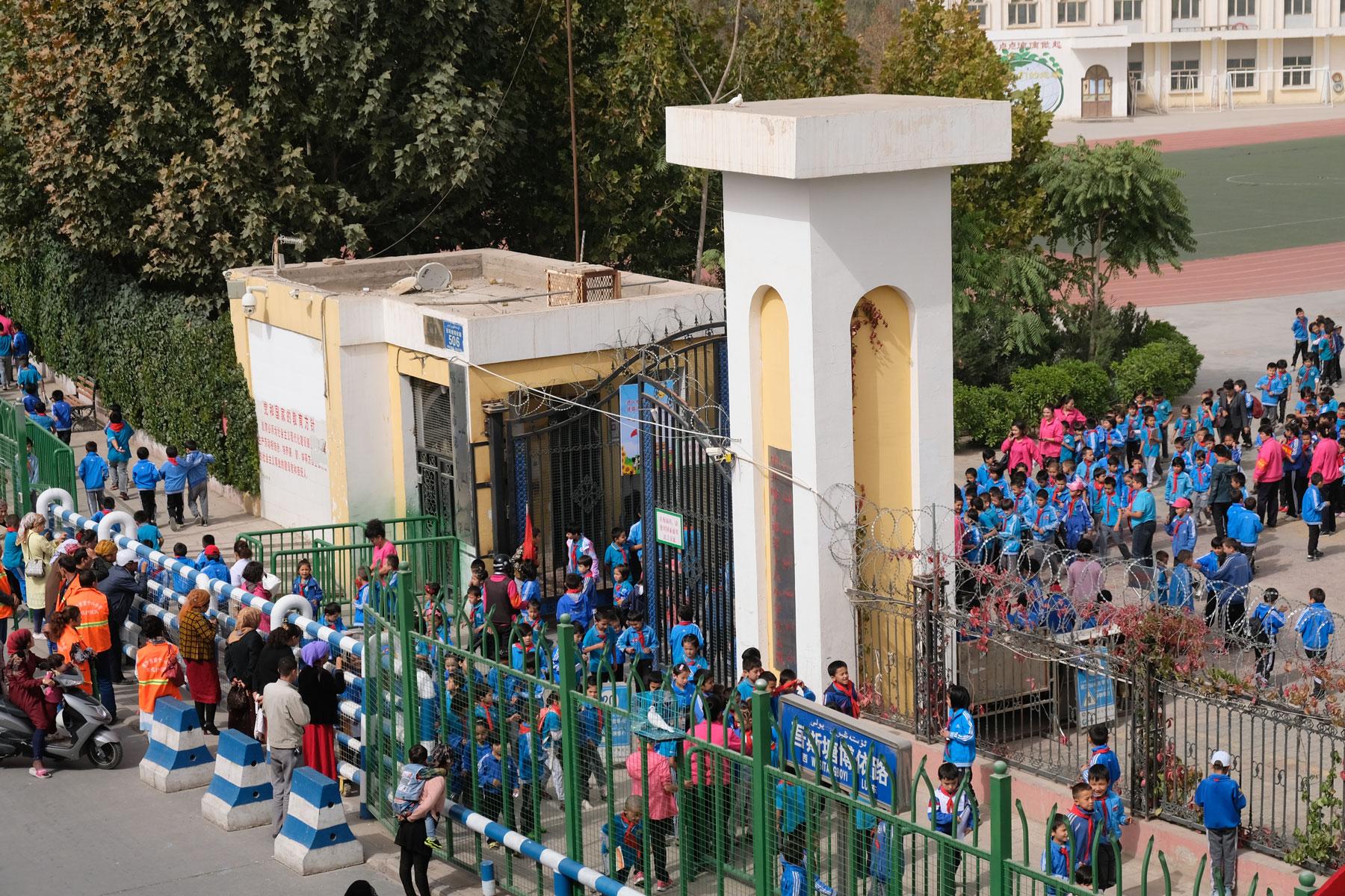 Vom Zimmer aus können wir auf die benachbarte Schule blicken, die mit Stacheldraht und Sicherheitsschleuse unliebsame Besucher fern hält