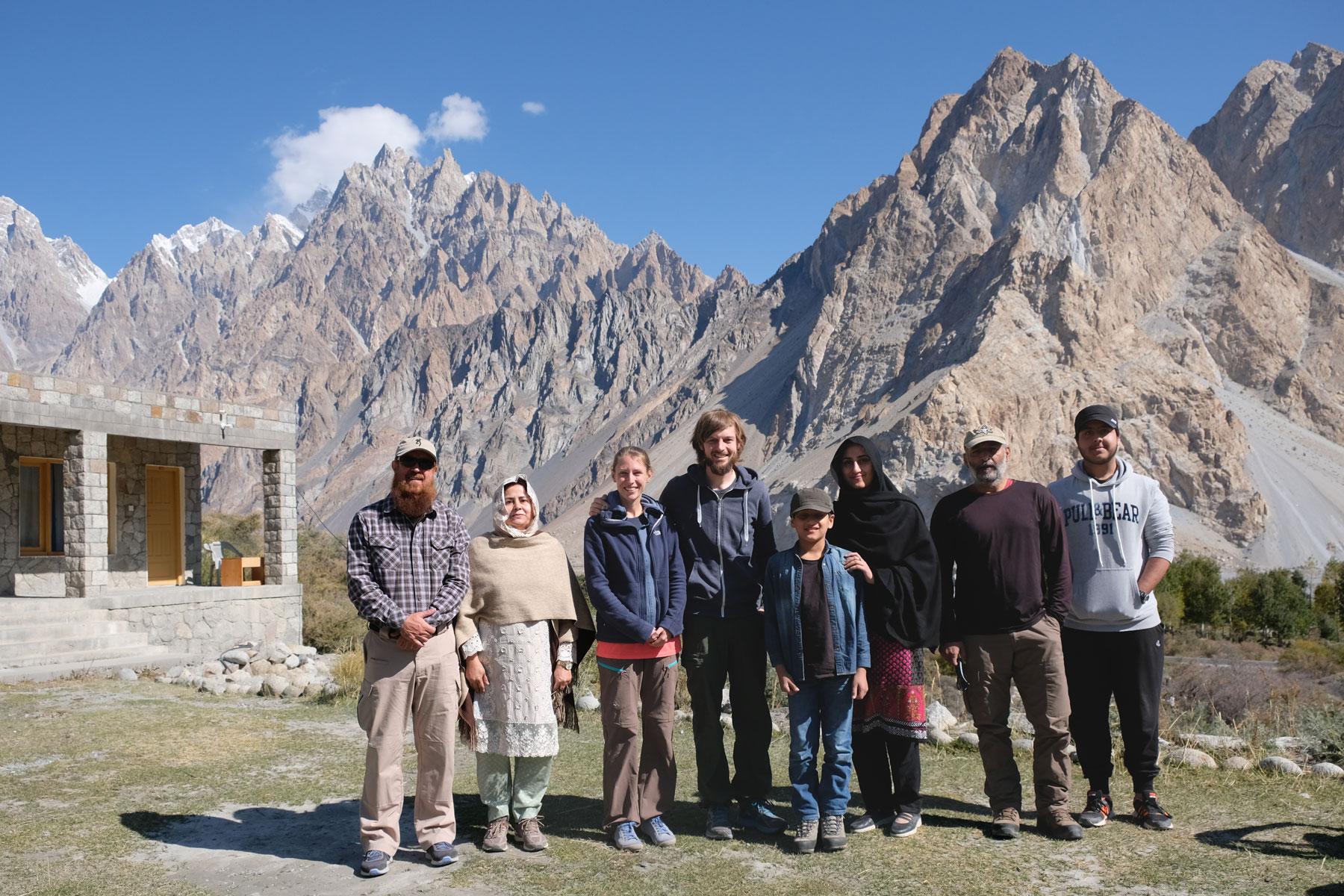 Leo und Sebastian mit einer pakistanischen Familie vor hohen Bergen.