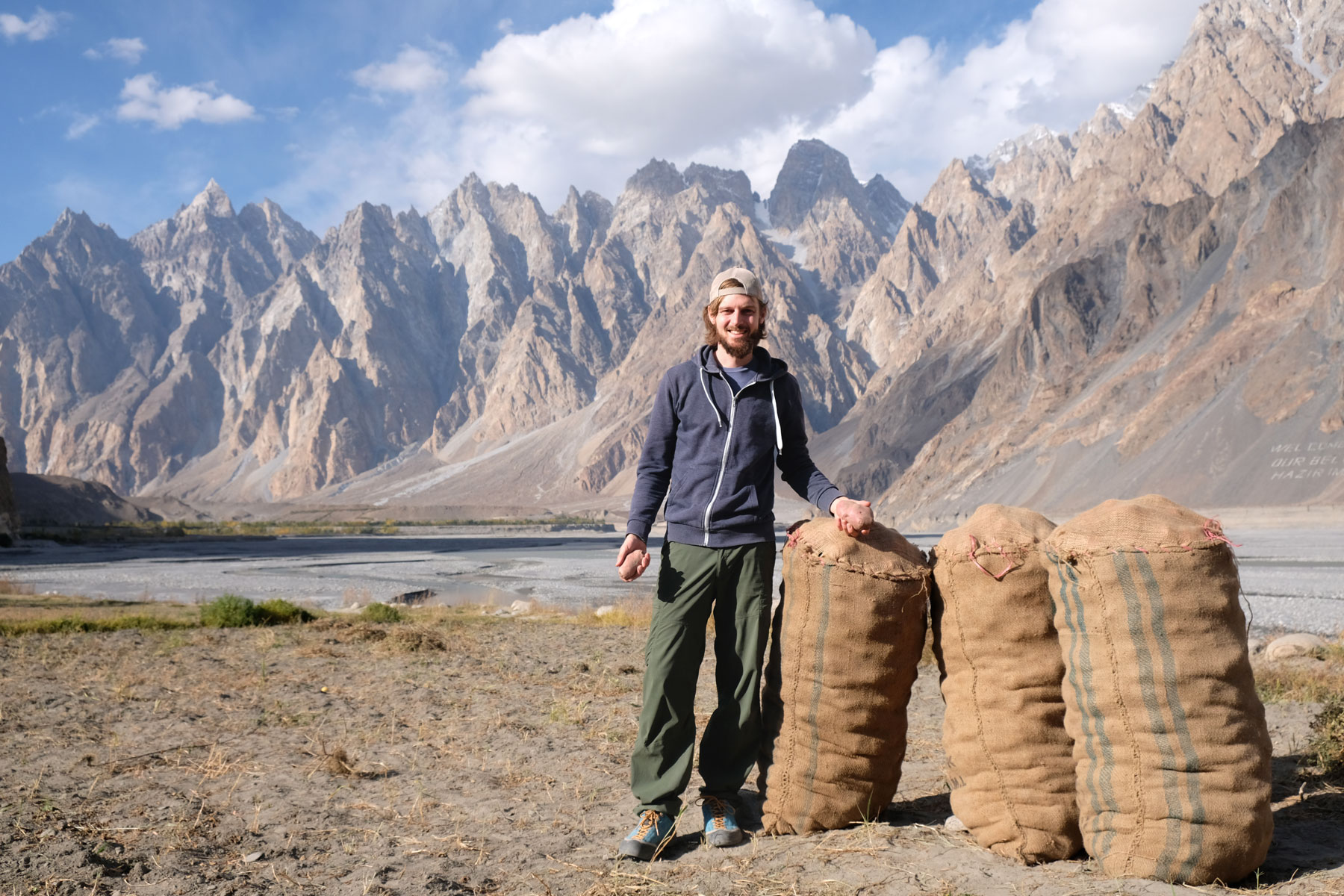 Sebastian neben drei Kartoffelsäcken im pakistanischen Karakorum.