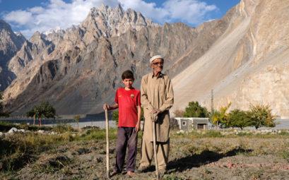Ein alter Mann steht neben einem Jungen auf einem Feld im Karakorumgebirge.