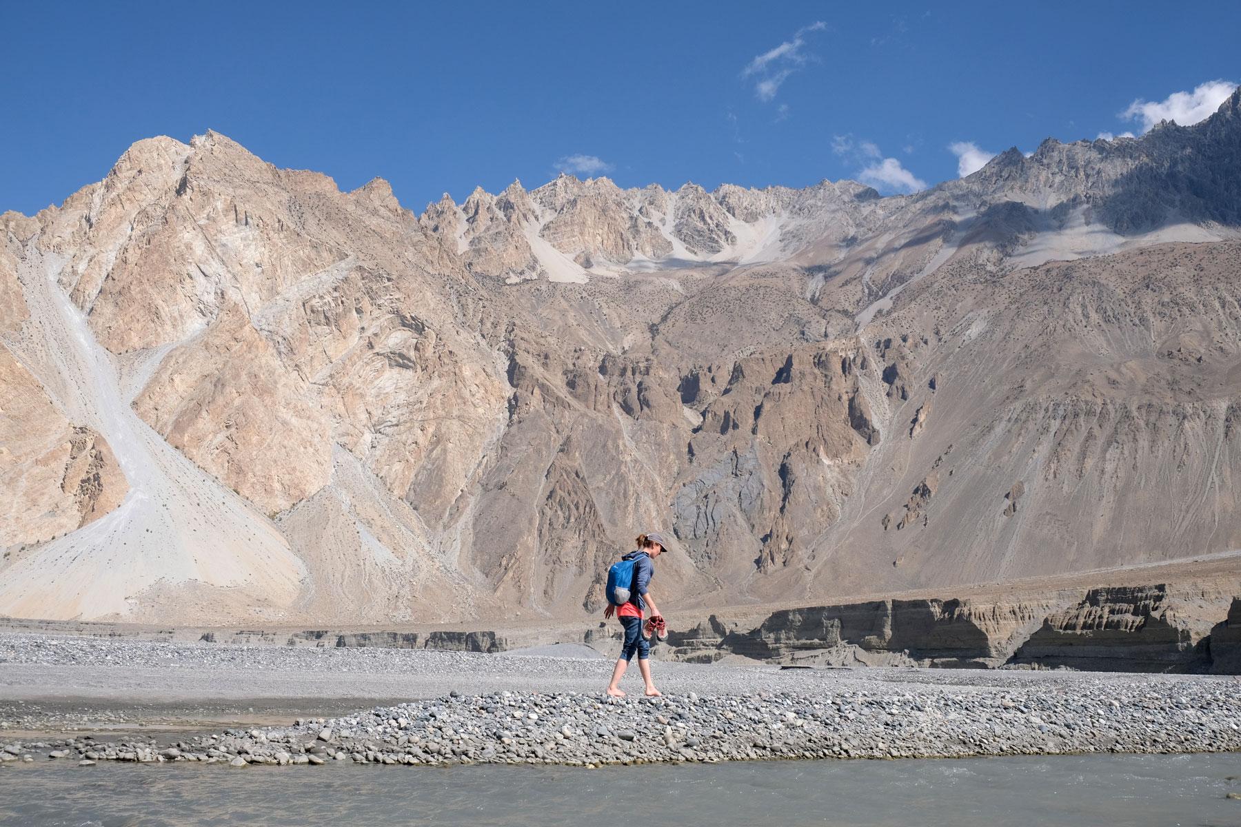 Leo läuft barfuß auf dem steinigen Ufer des Hunza-Flusses.