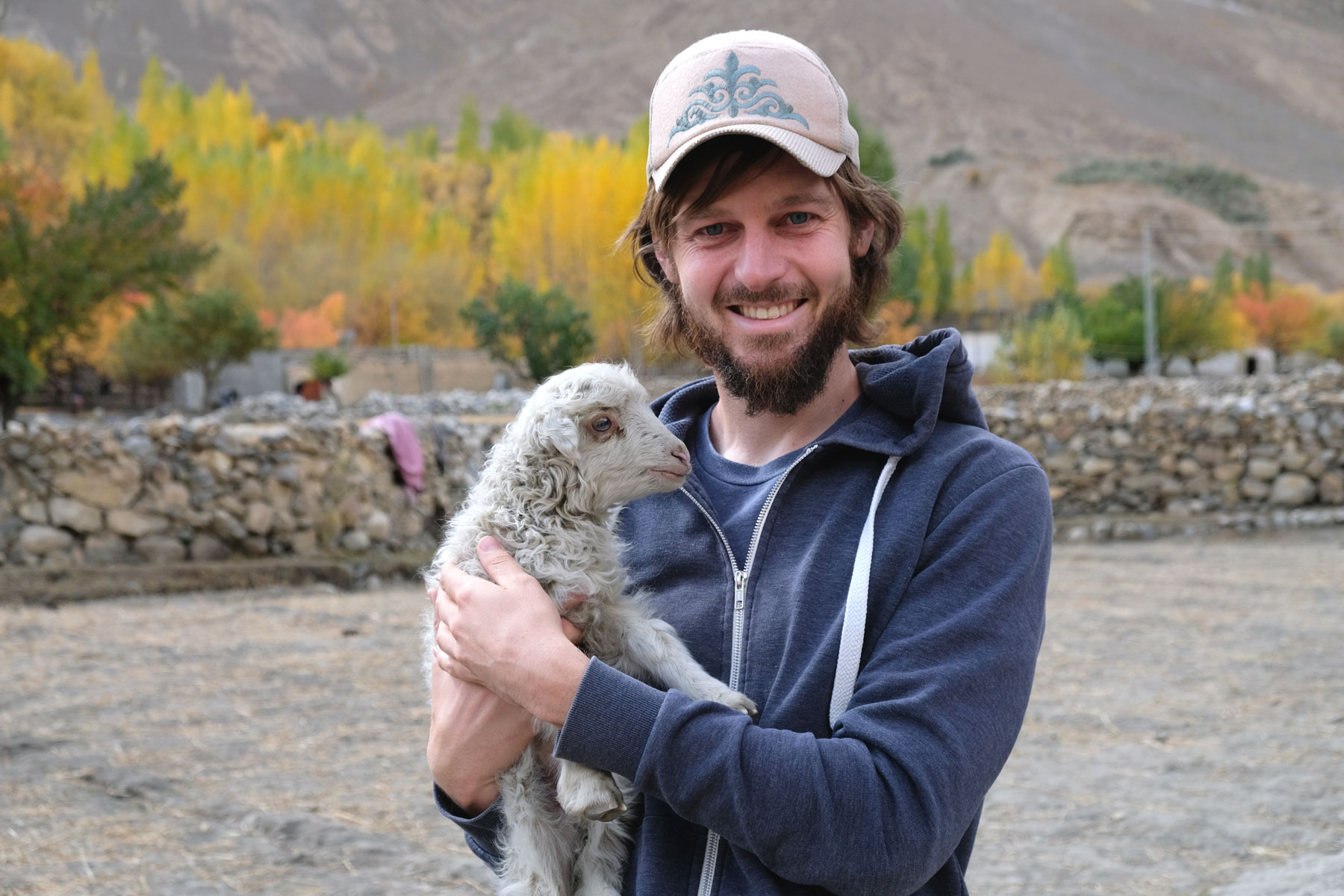 Sebastian hält ein Lamm auf dem Arm.