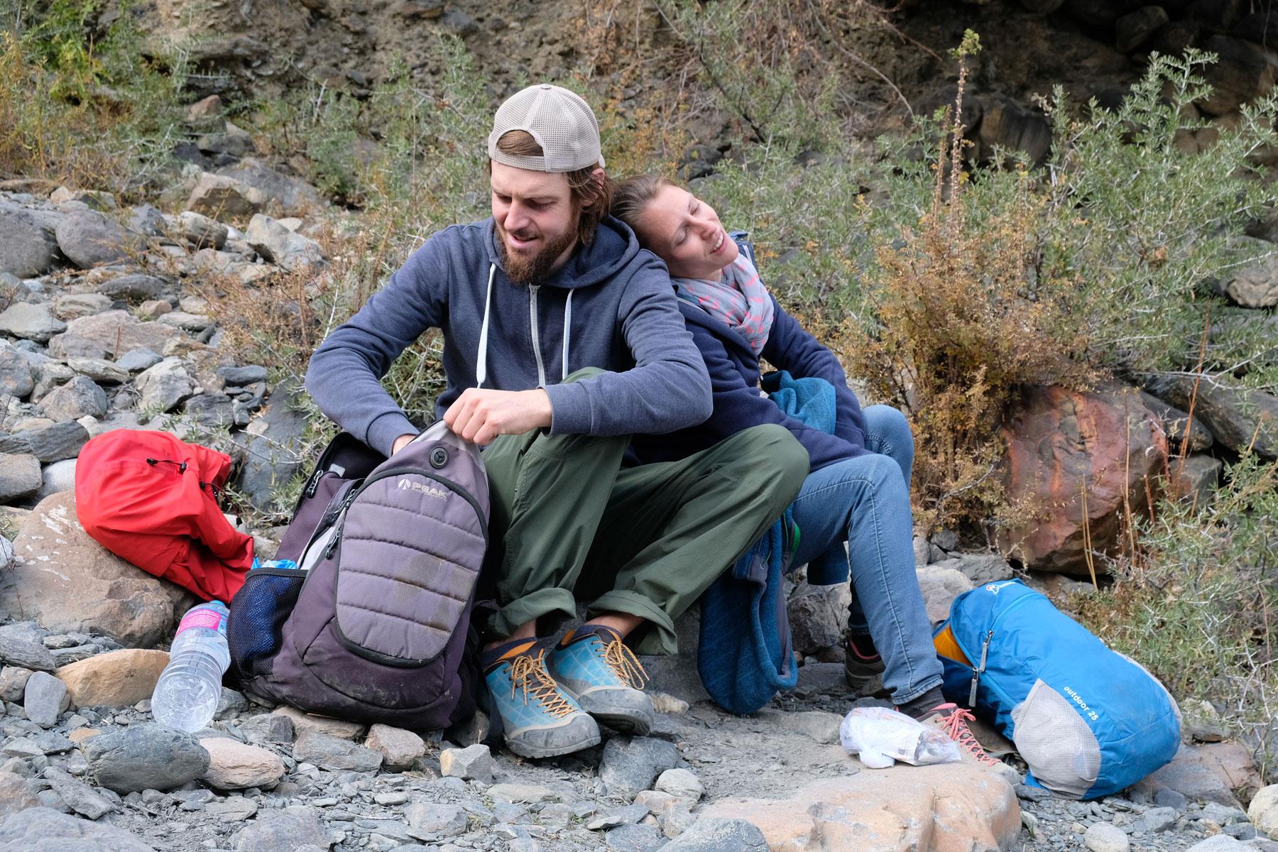 Sebastian und Leo sitzen auf Steinen und hole etwas aus einem Rucksack.