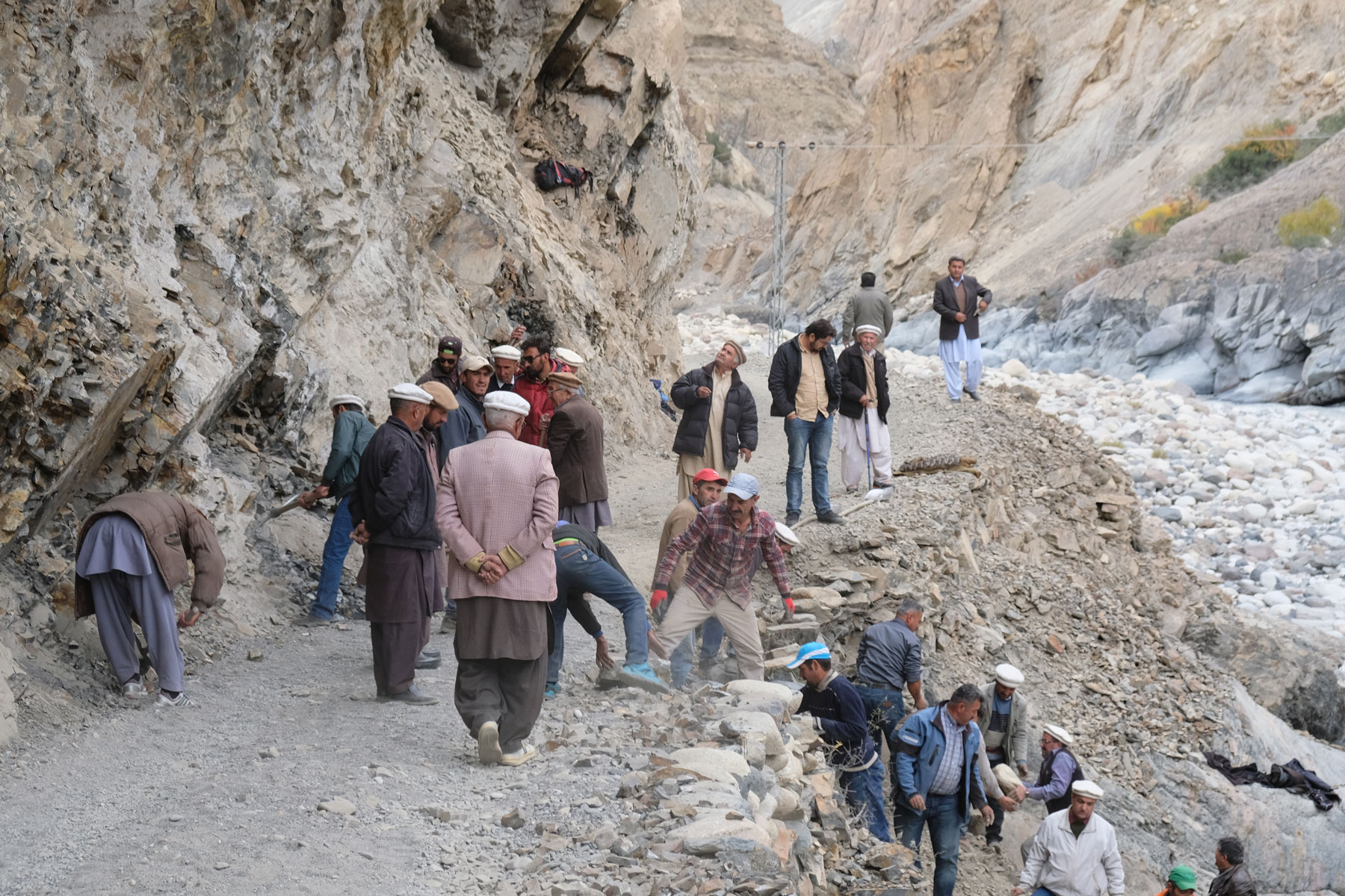 Pakistanische Männer reparieren eine Gebirgsstraße im Karakorumgebirge.
