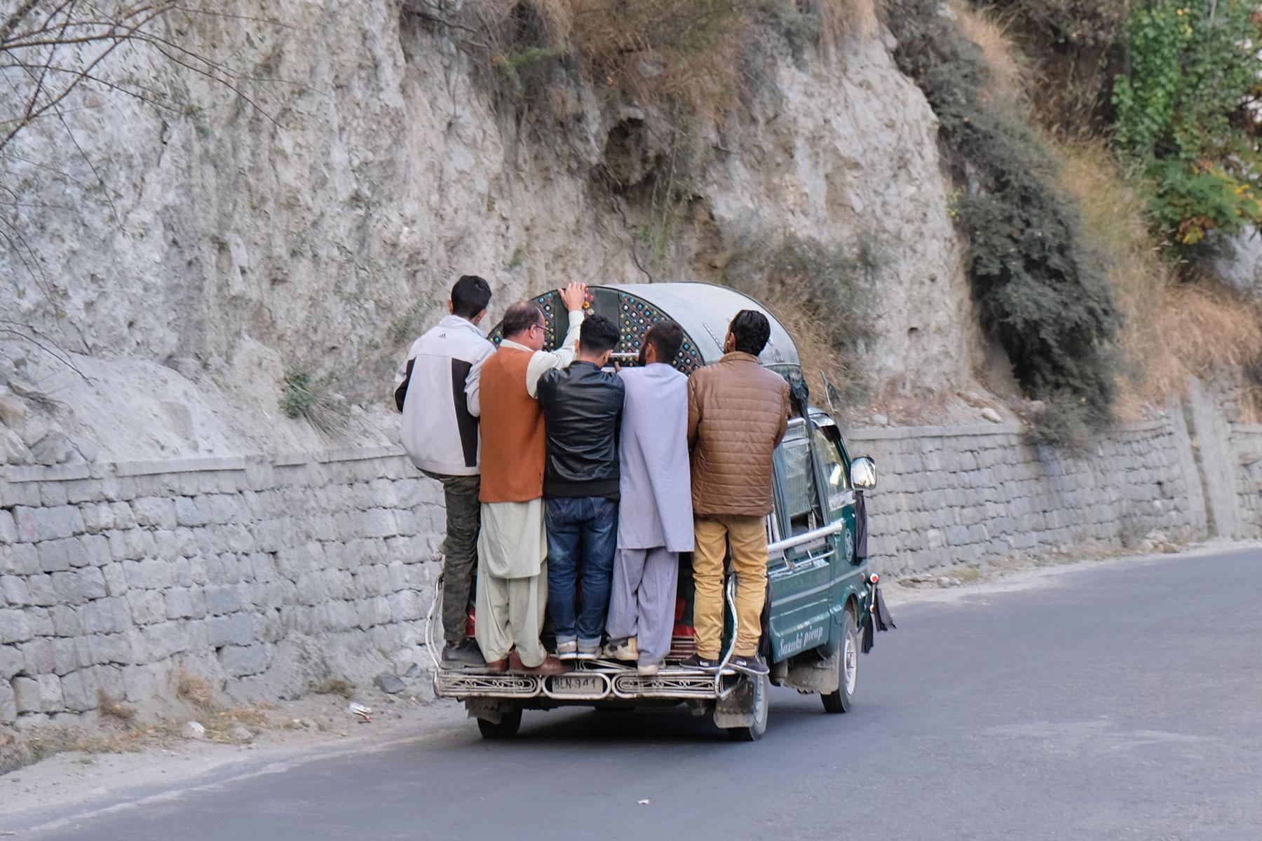 Männer stehen auf der Stoßstange eines Kleintransporters.