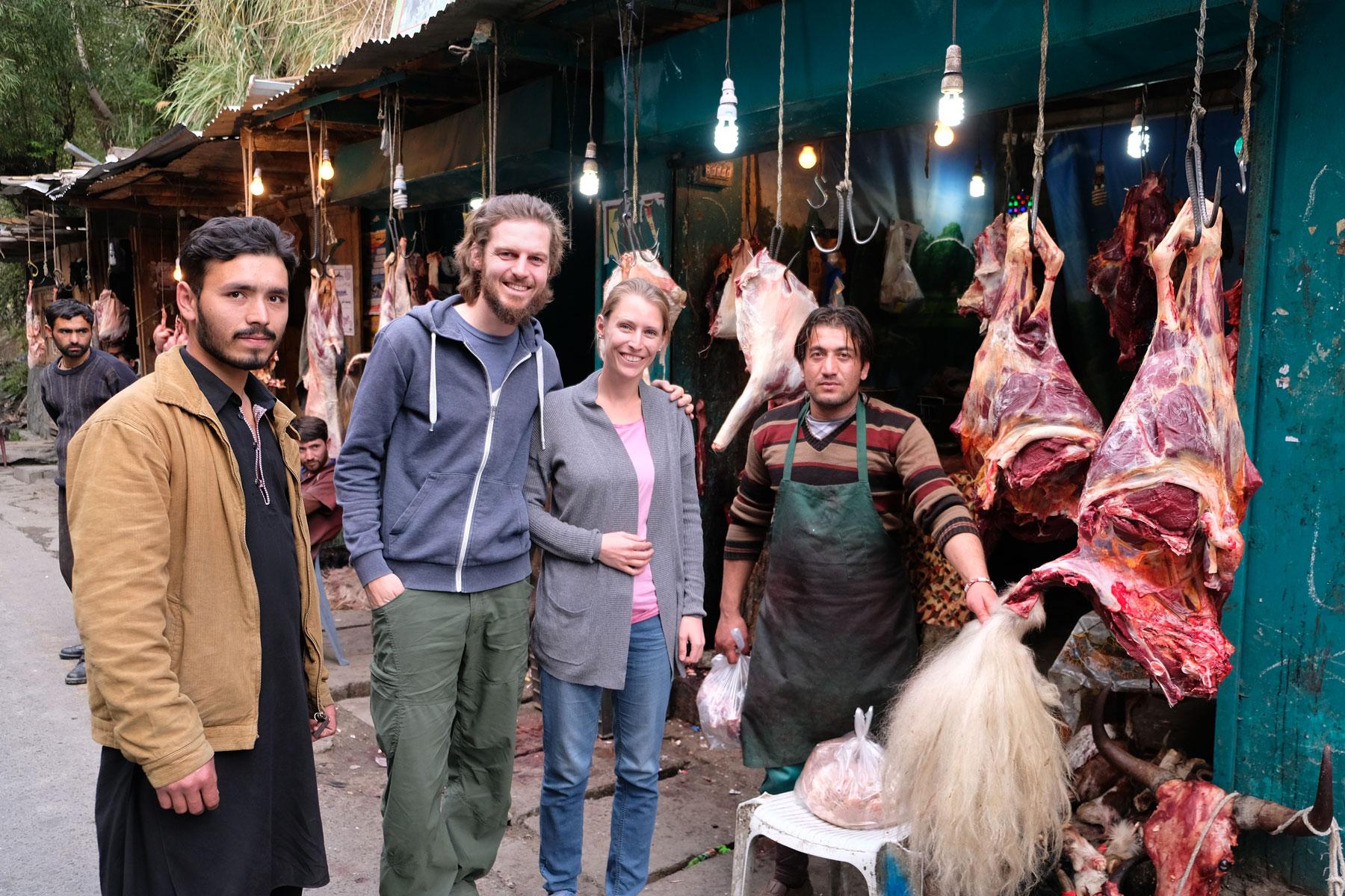 Sebastian und Leo stehen neben zwei Männern an einem Fleischstand, an dem Yakfleisch verkauft wird.
