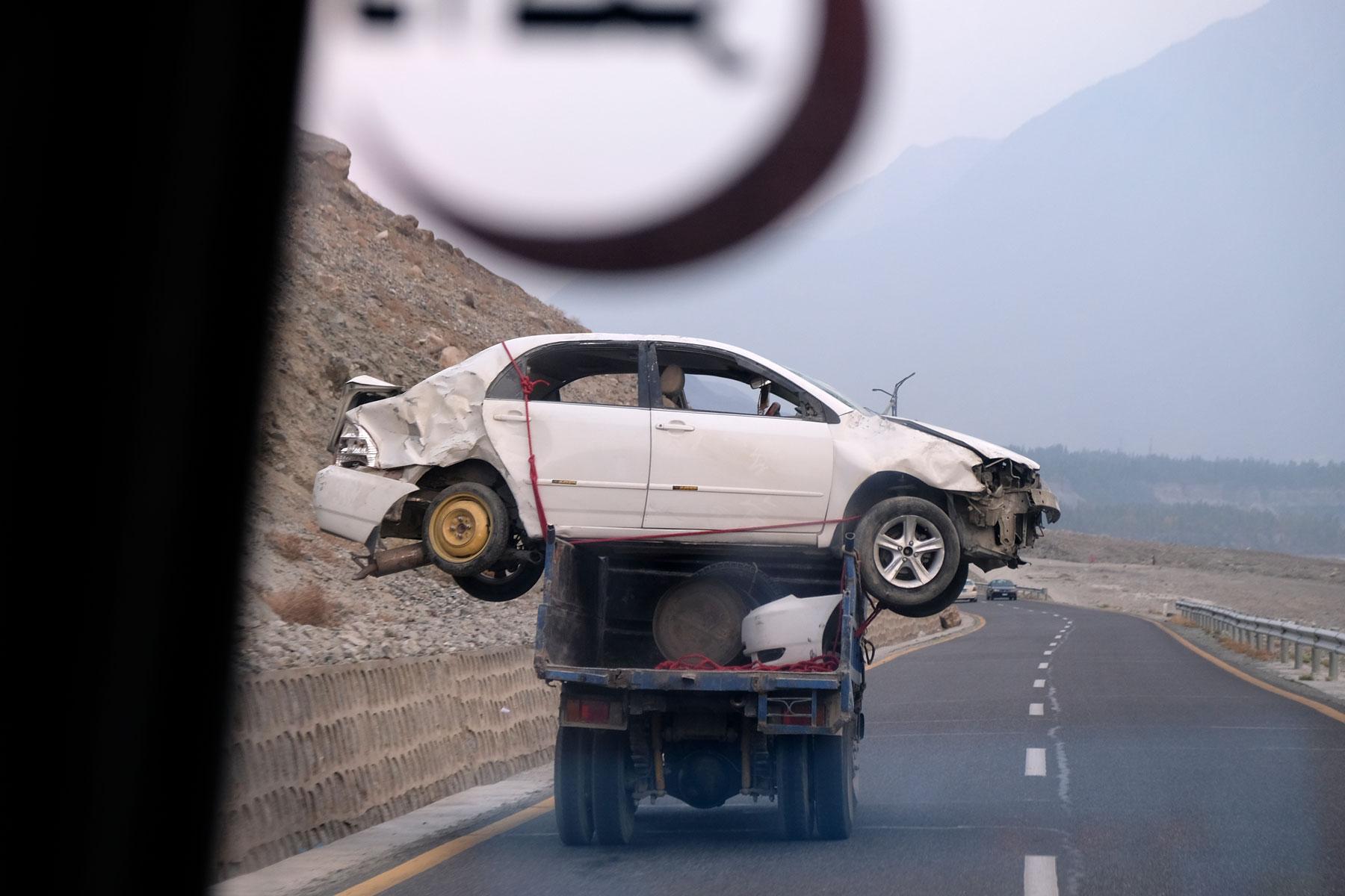 Ein kaputtes Auto wird auf der Ladefläche eines Lastwagens abgeschleppt.