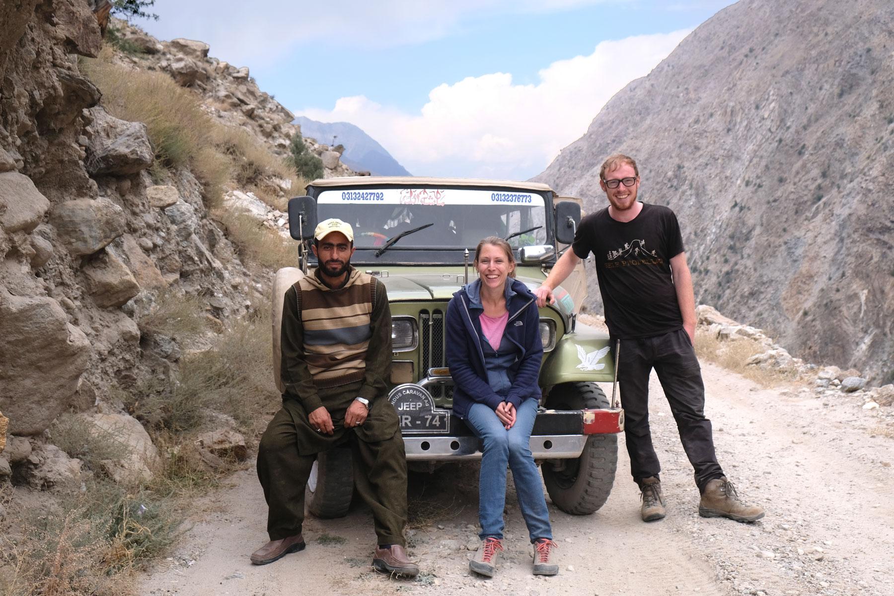 Leo sitzt neben zwei Männern auf der Stoßstange eines Geländewagens.
