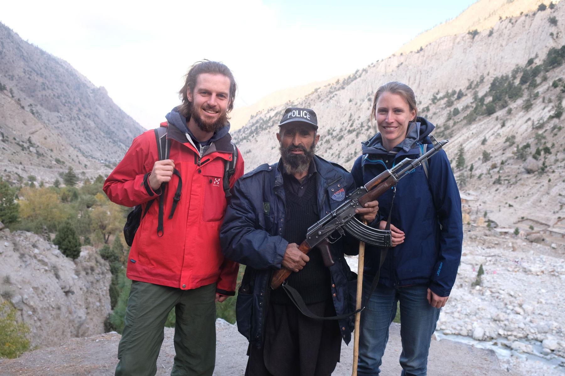 Sebastian und Leo neben einem Mann mit Maschinengewehr.