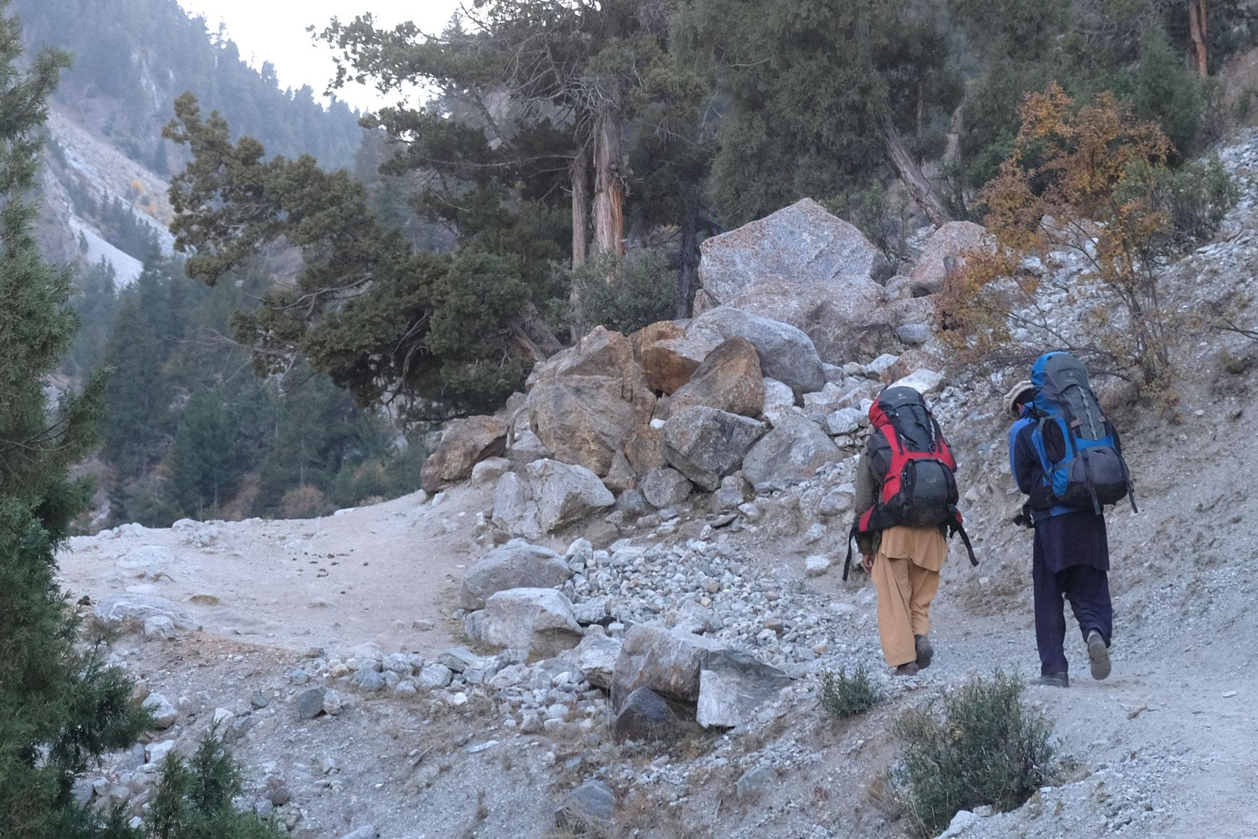 Zwei Männer tragen Reiserucksäcke auf einem Pfad bergauf.