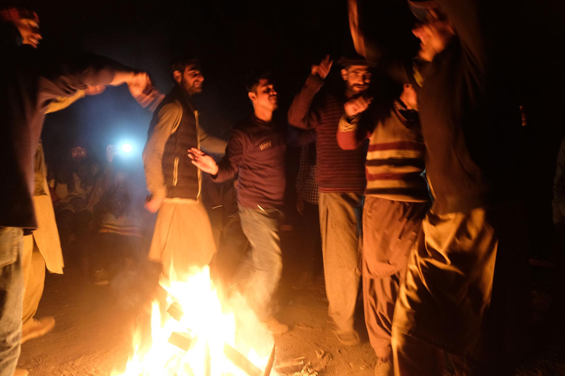 Männer tanzen in Fairy Meadows um ein Lagerfeuer.