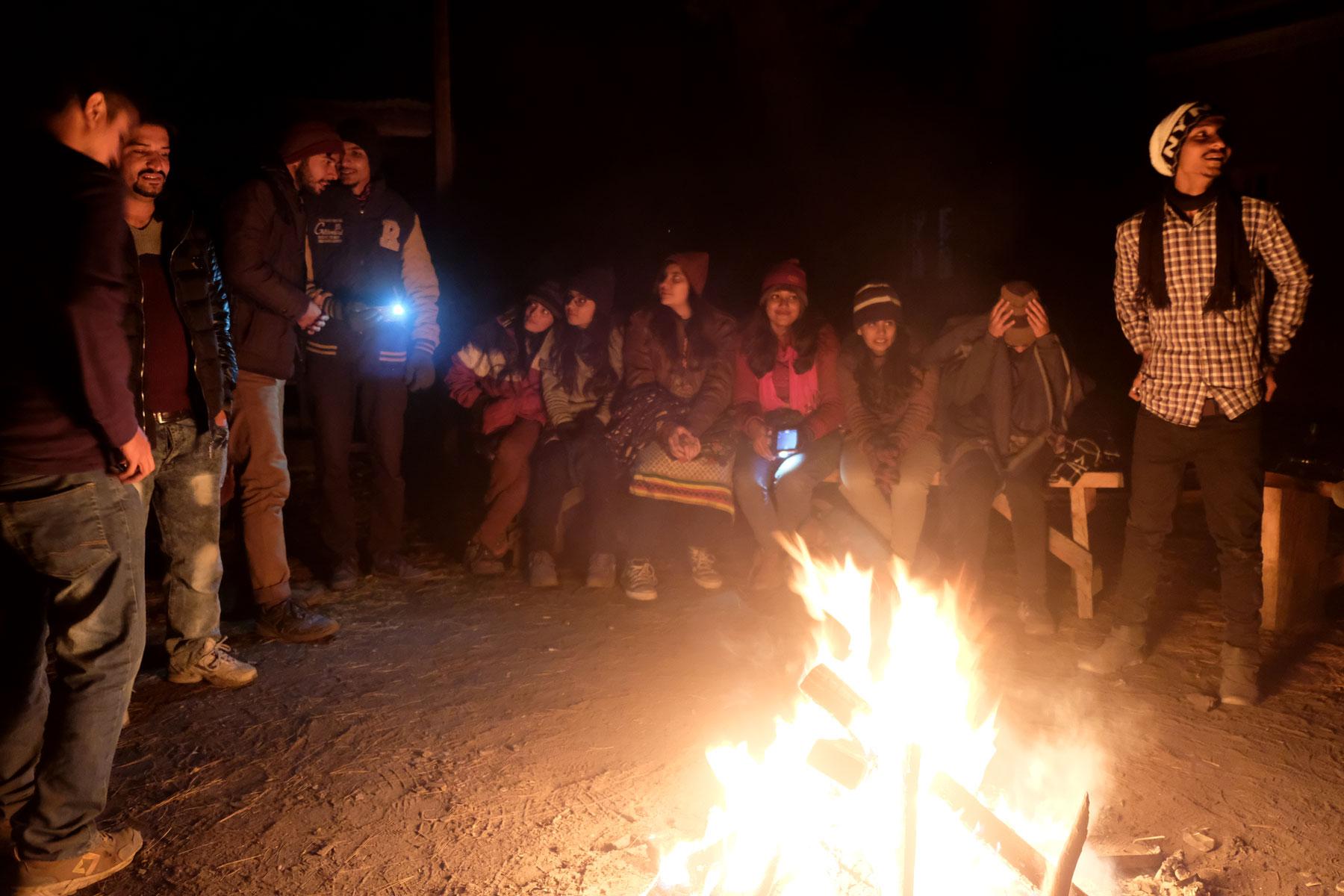 Menschen sitzen und stehen um ein Lagerfeuer in Fairy Meadows.
