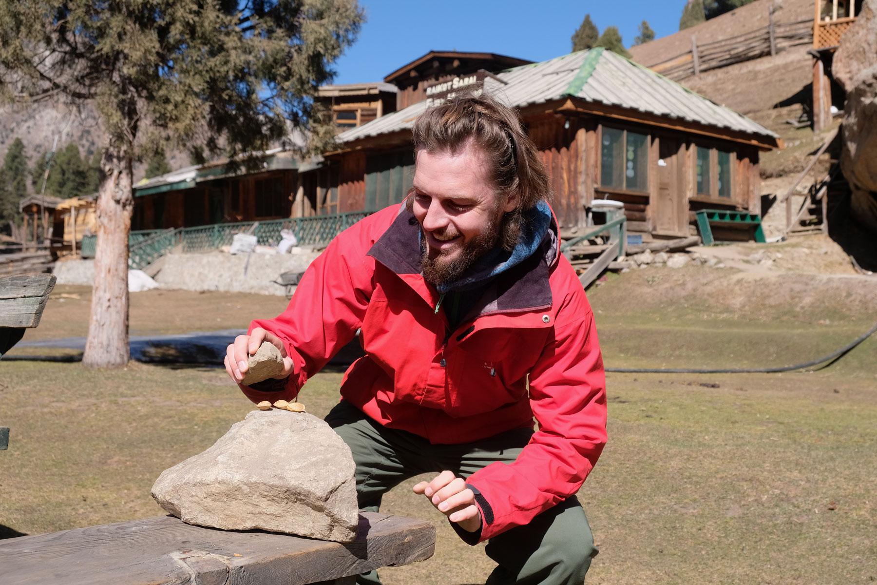 Sebastian knackt Mandeln mit einem Stein.