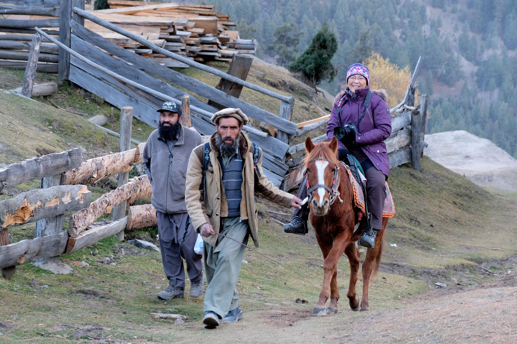 Zwei Männer führen eine Frau, die auf einem Pferd sitzt, nach Fairy Meadows.