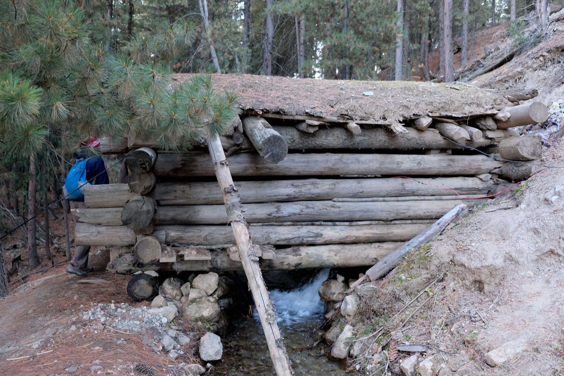 Holzhütte an einem Bach.