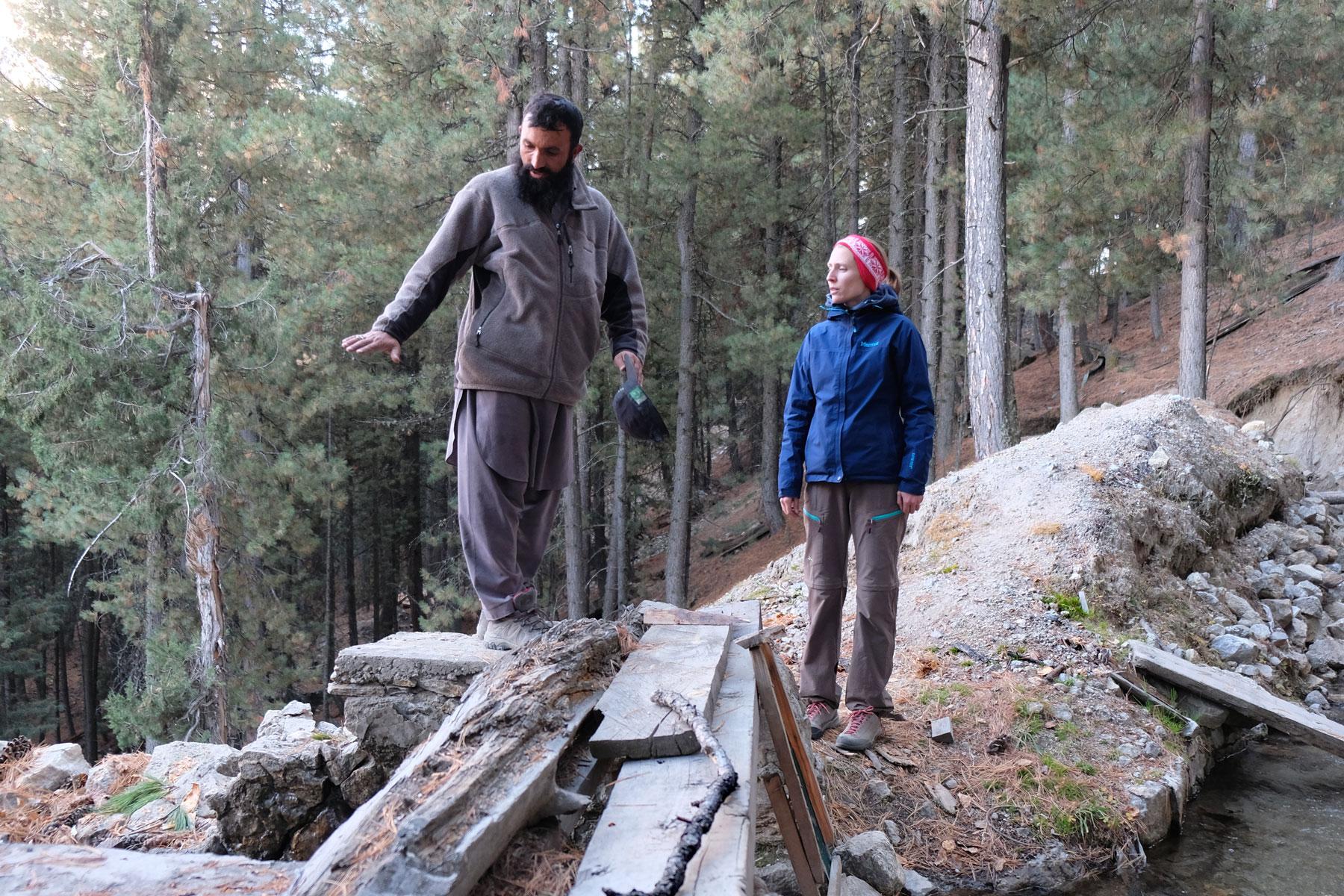 Leo steht im Wald neben einem Pakistaner, der ihr etwas erklärt.