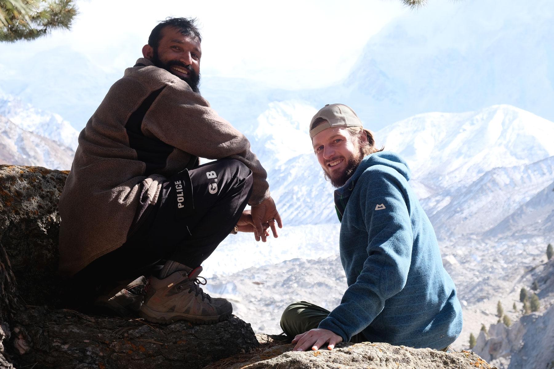 Sebastian hockt neben einem bärtigen Pakistaner.