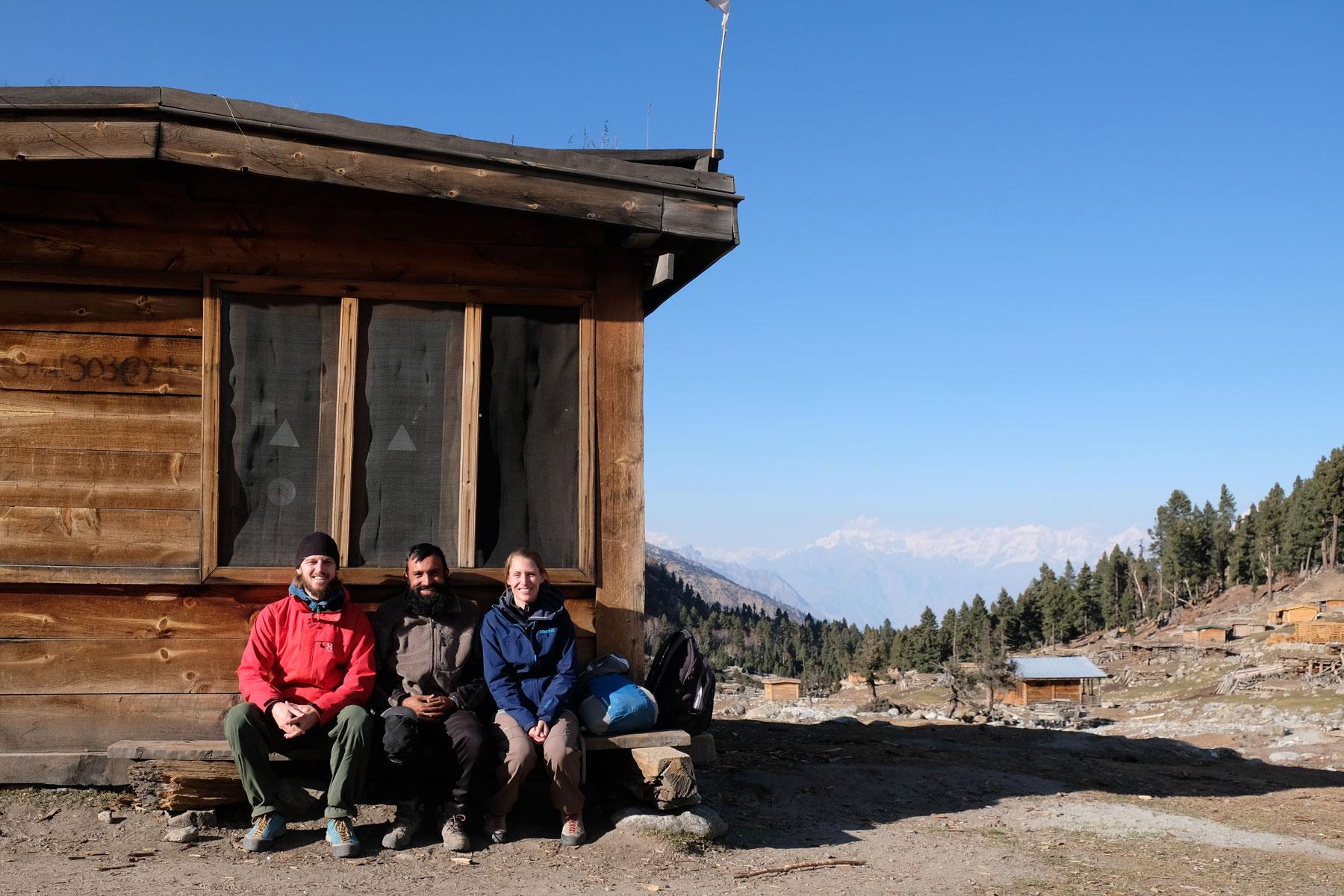 Sebastian und Leo sitzen mit einem pakistansichen Mann vor einer Holzhütte.