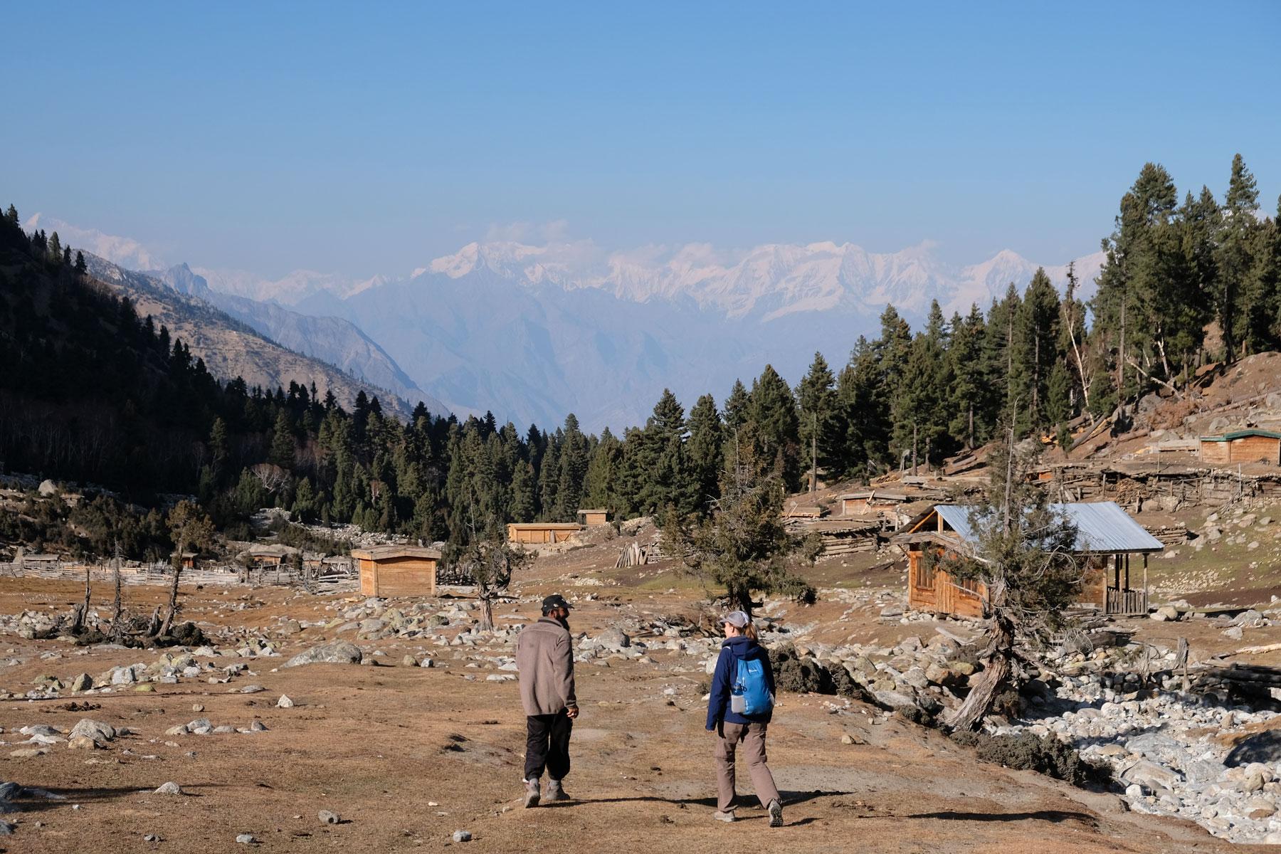 Leo geht neben einem pakistansichen Mann im Gebirge.