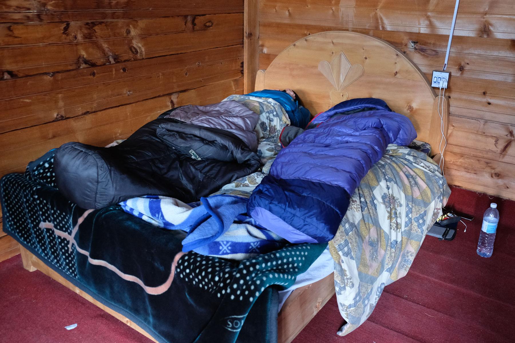 Ein Bett, auf dem zwei Winterschlafsäcke liegen.