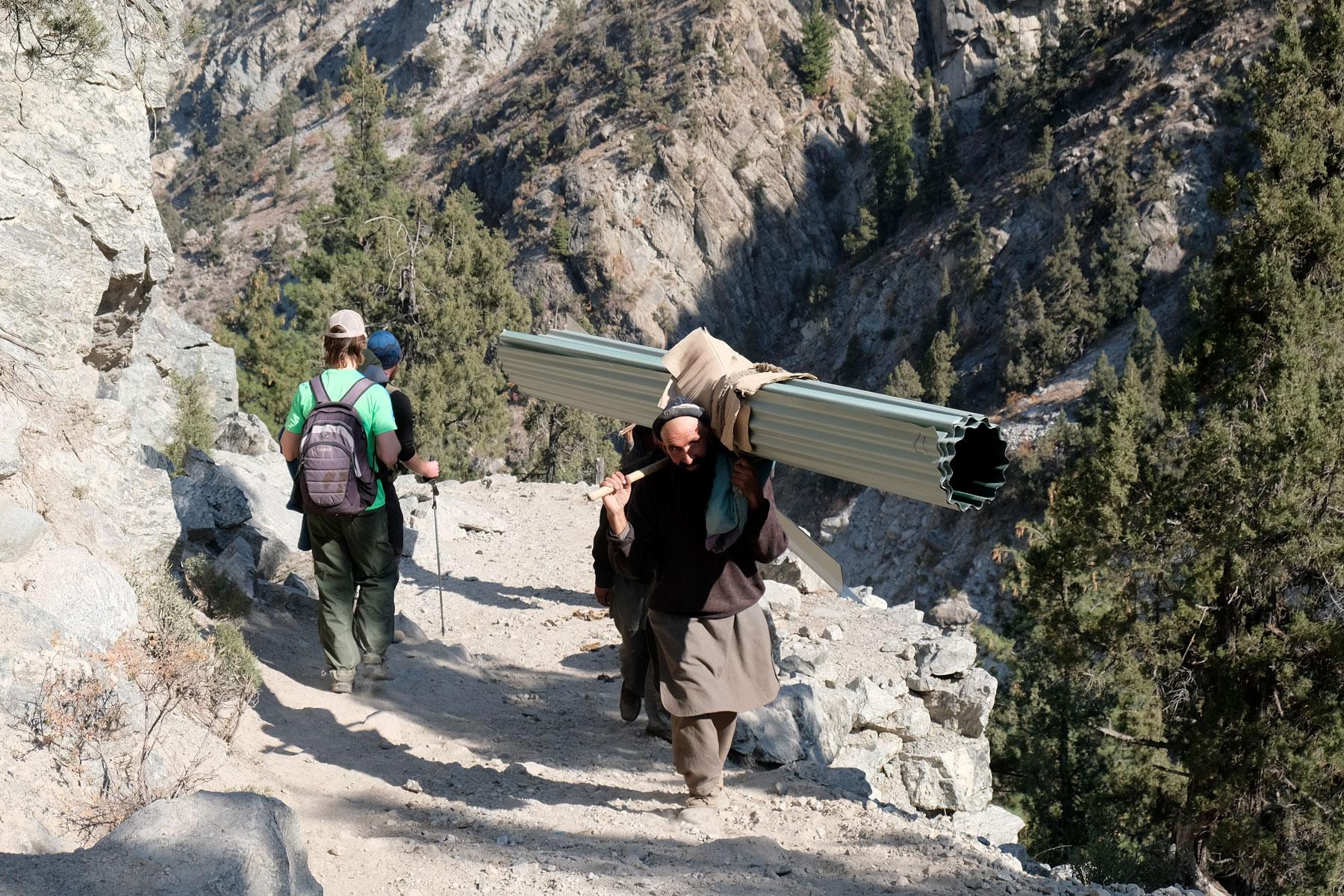 Zwei Männer tragen im Karakorumgebirge eine zusammengerollte Metallplane.