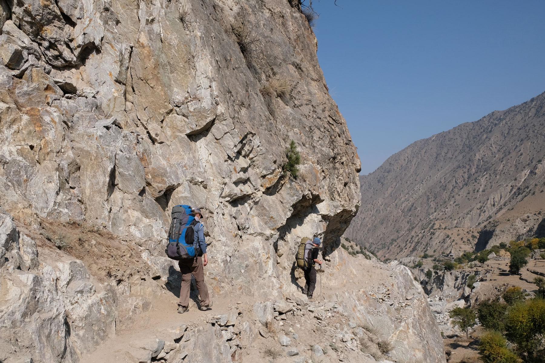 Leo und ein Mann gehen auf einem schmalen Pfad im Gebirge.