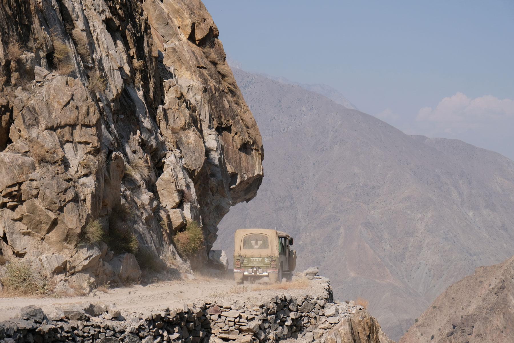 Ein Geländewagen fährt über eine Schotterstraße im Gebirge.