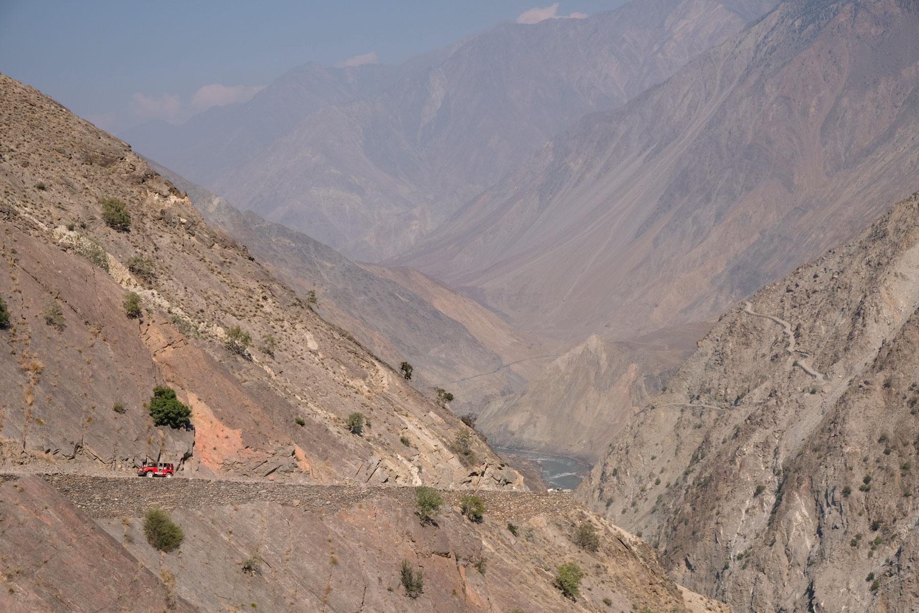 Ein roter Geländewagen auf einer schmalen Gebirgsstraße im Karakorumgebirge.
