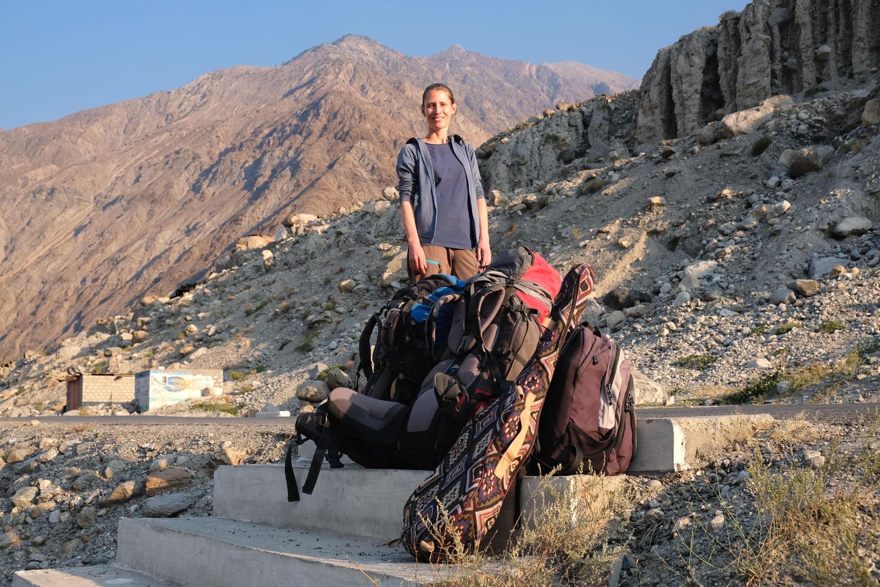 Leo steht vor Reisegepäck im Gebirge.