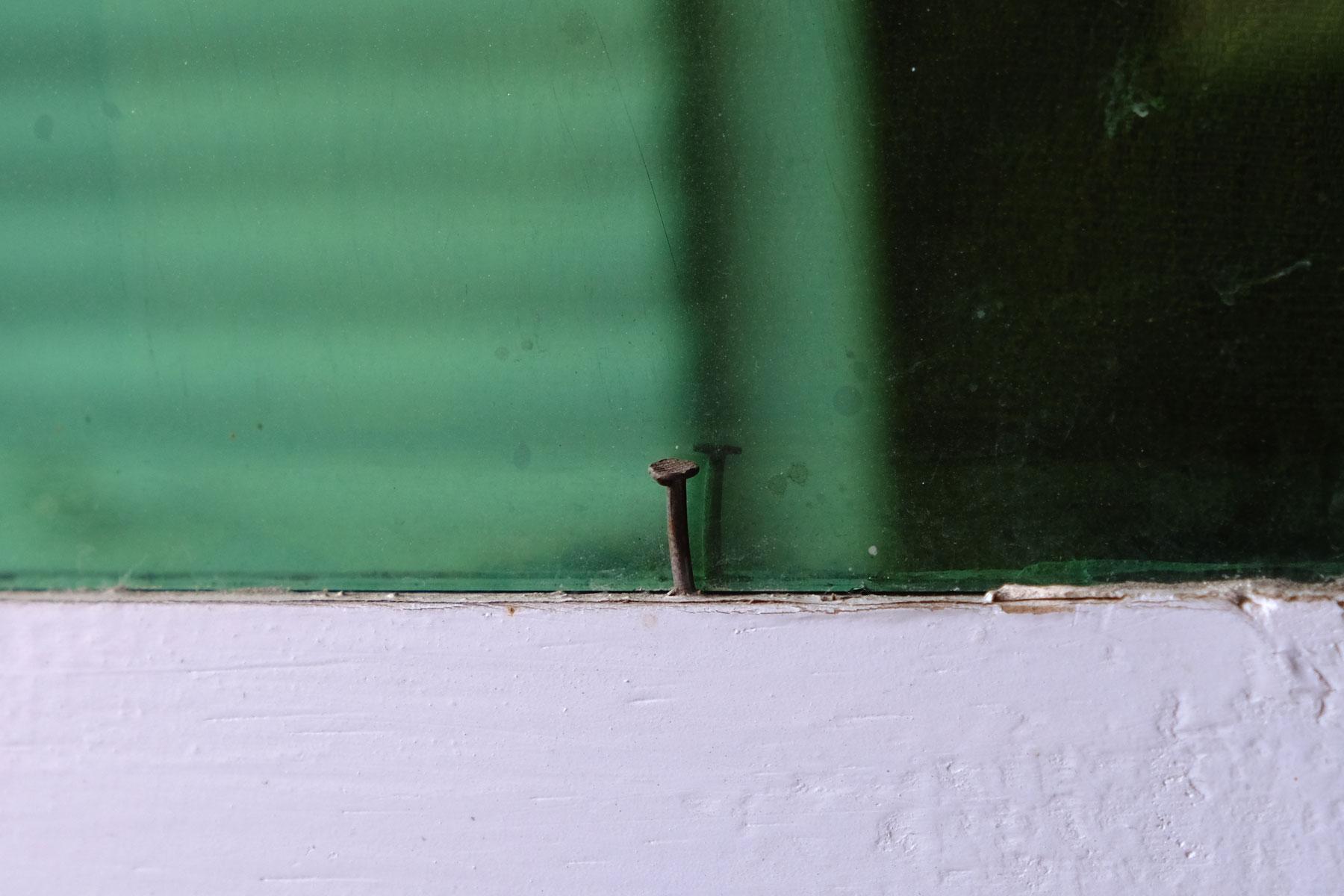 Eine Fensterscheibe, die mit einem Nagel befestigt ist.