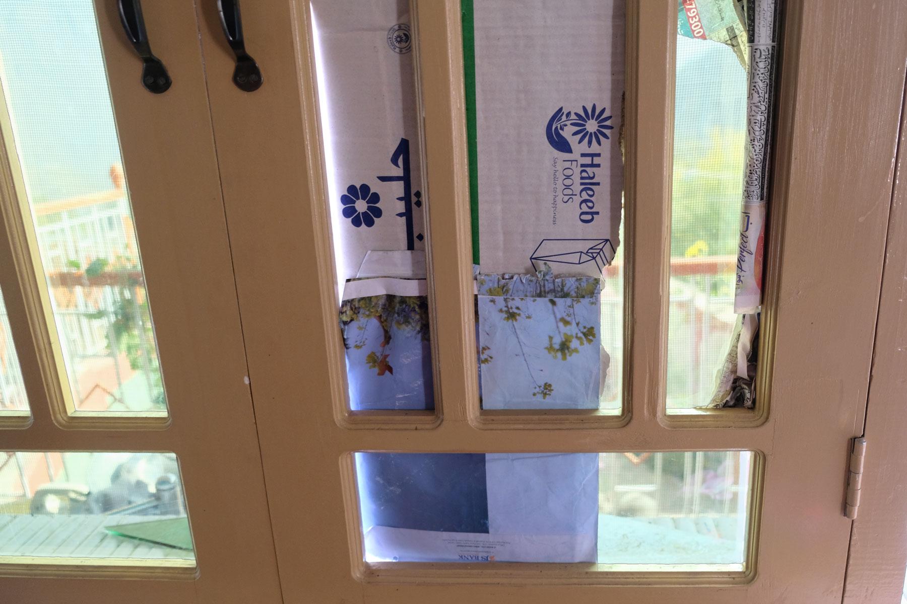 Ein Fenster, dessen Scheiben durch Karton ersetzt wurden.