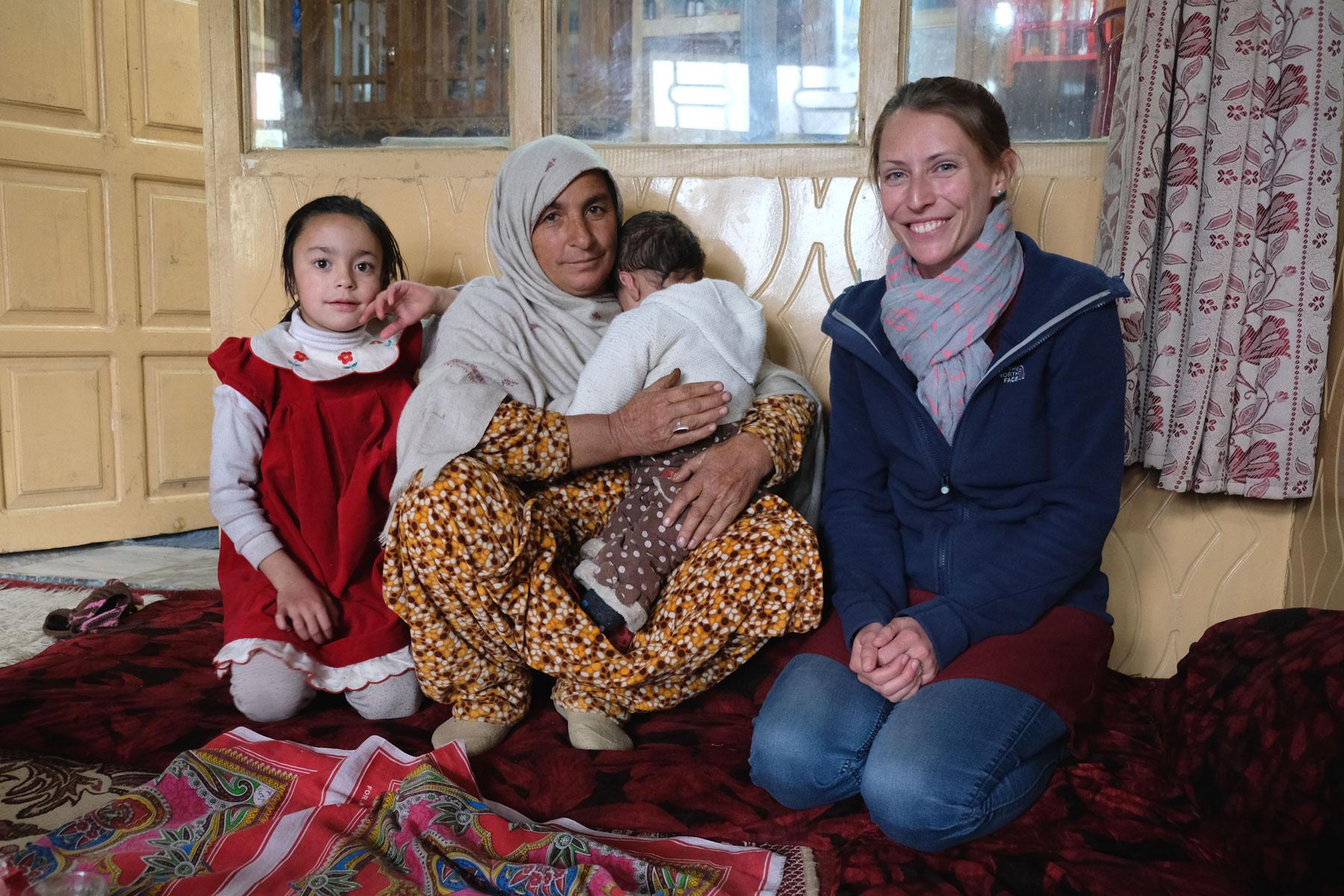 Leo neben einer pakistanischen Frau, die ein Baby auf dem Arm hält.