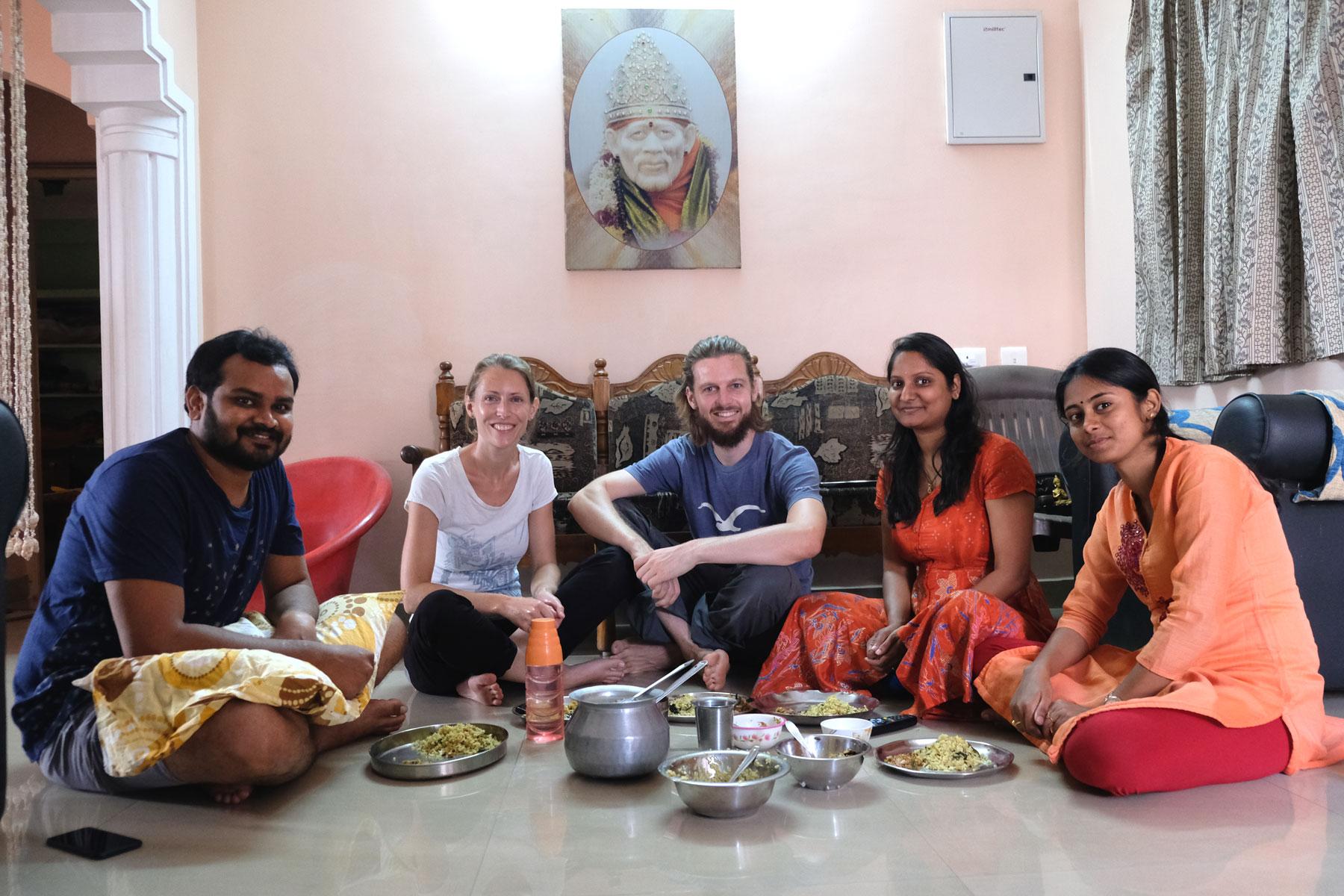 Leo und Sebastian sitzen mit indischen Freunden auf dem Boden und essen.
