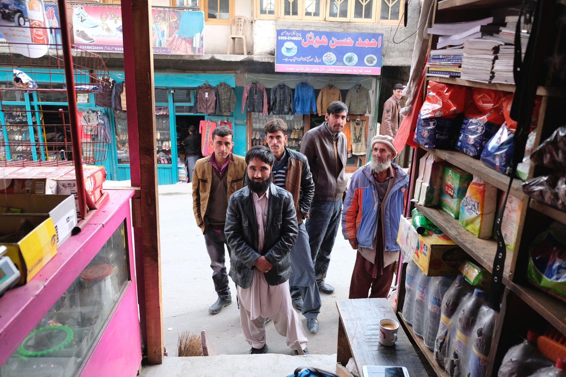 Pakistanische Männer schauen von außen in ein Geschäft in Astore.