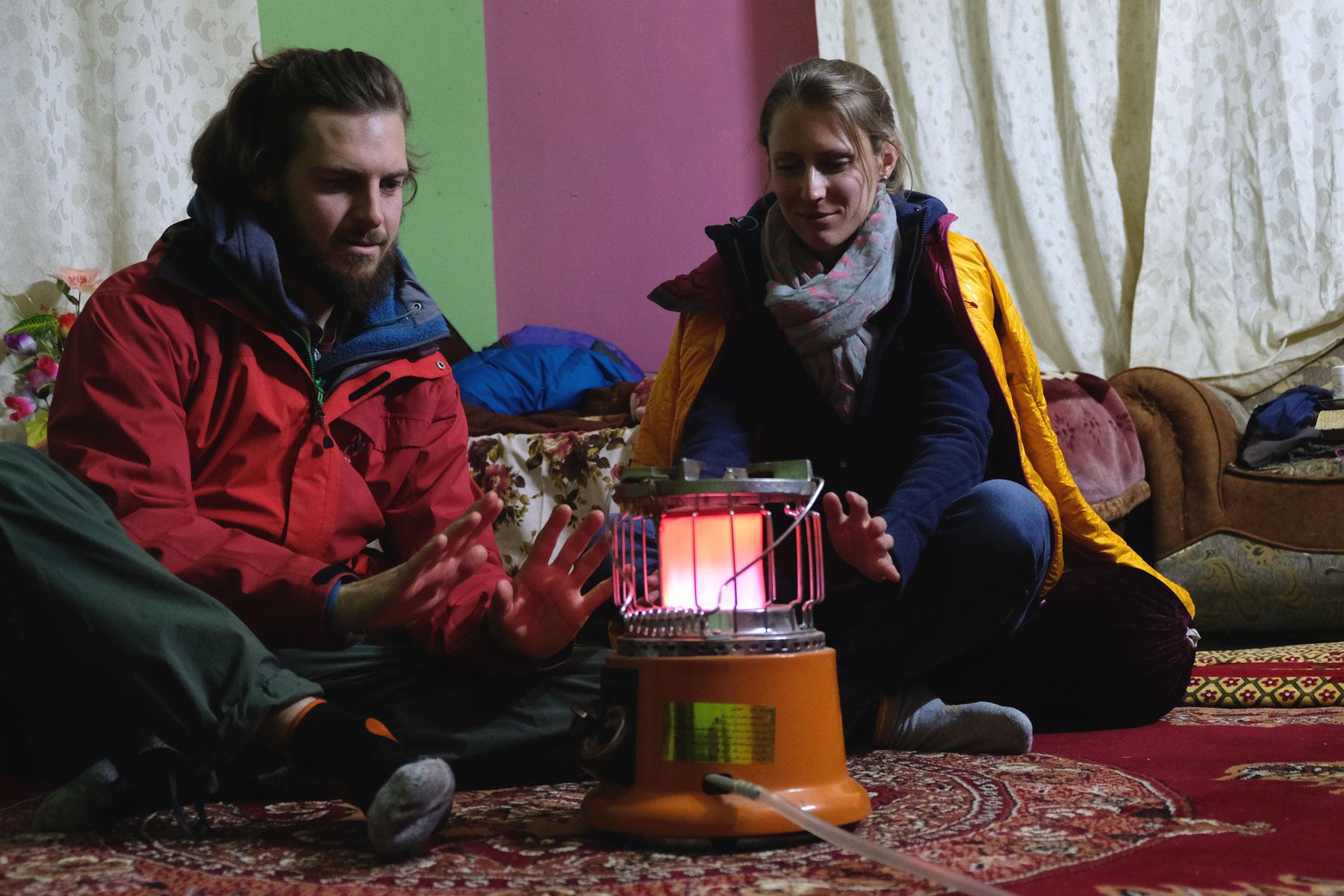 Sebastian und Leo sitzen in Jacken gehüllt um eine Gasheizung.