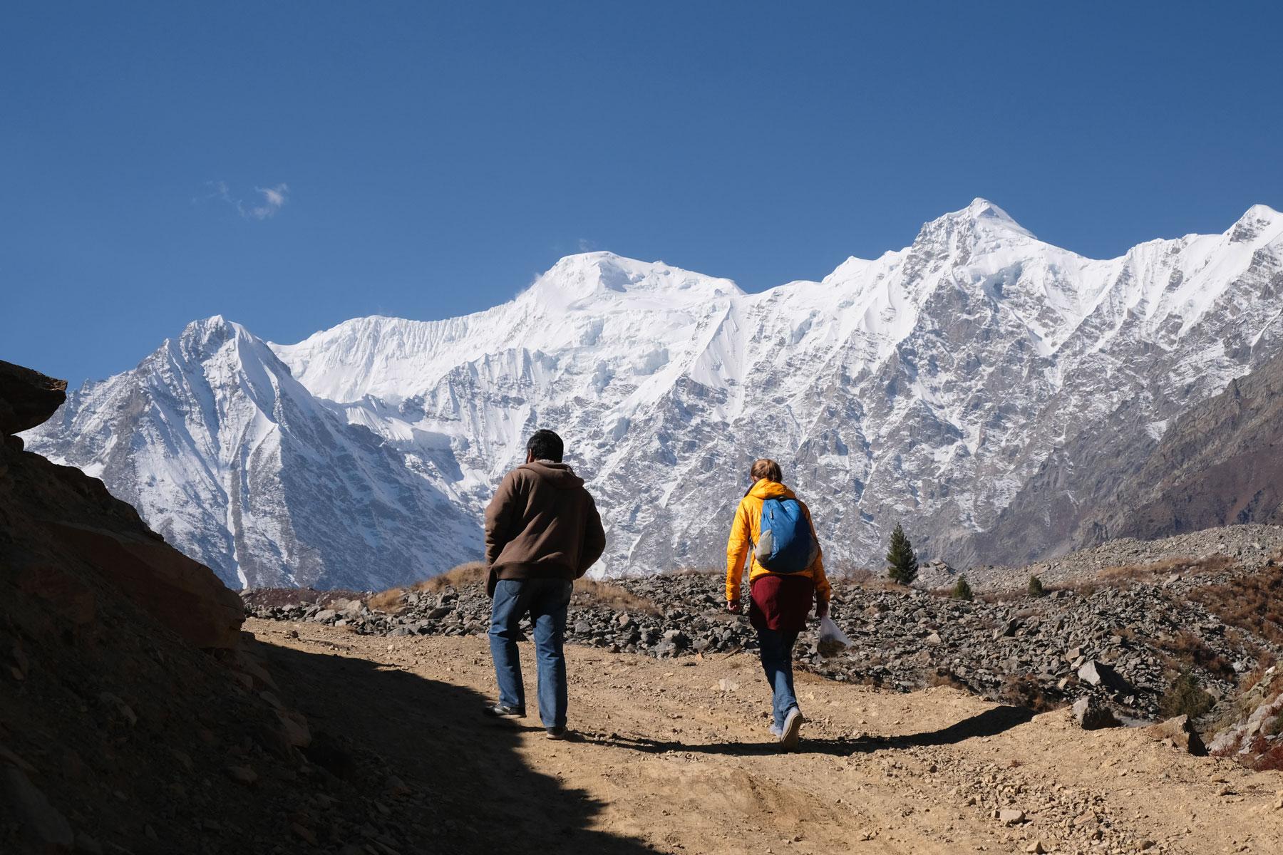 Leo geht neben einem Mann. Im Hitnergund sind schneebedeckte Berge.