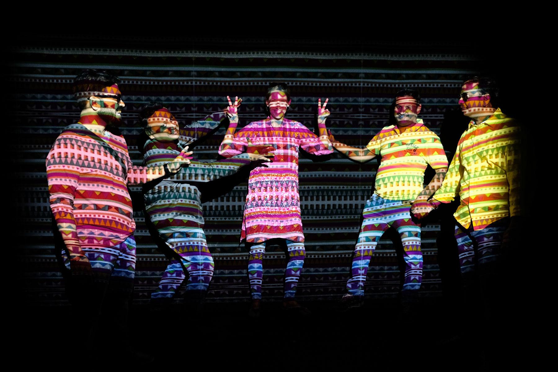 Leo und indische Männer in buntem Scheinwerferlicht.
