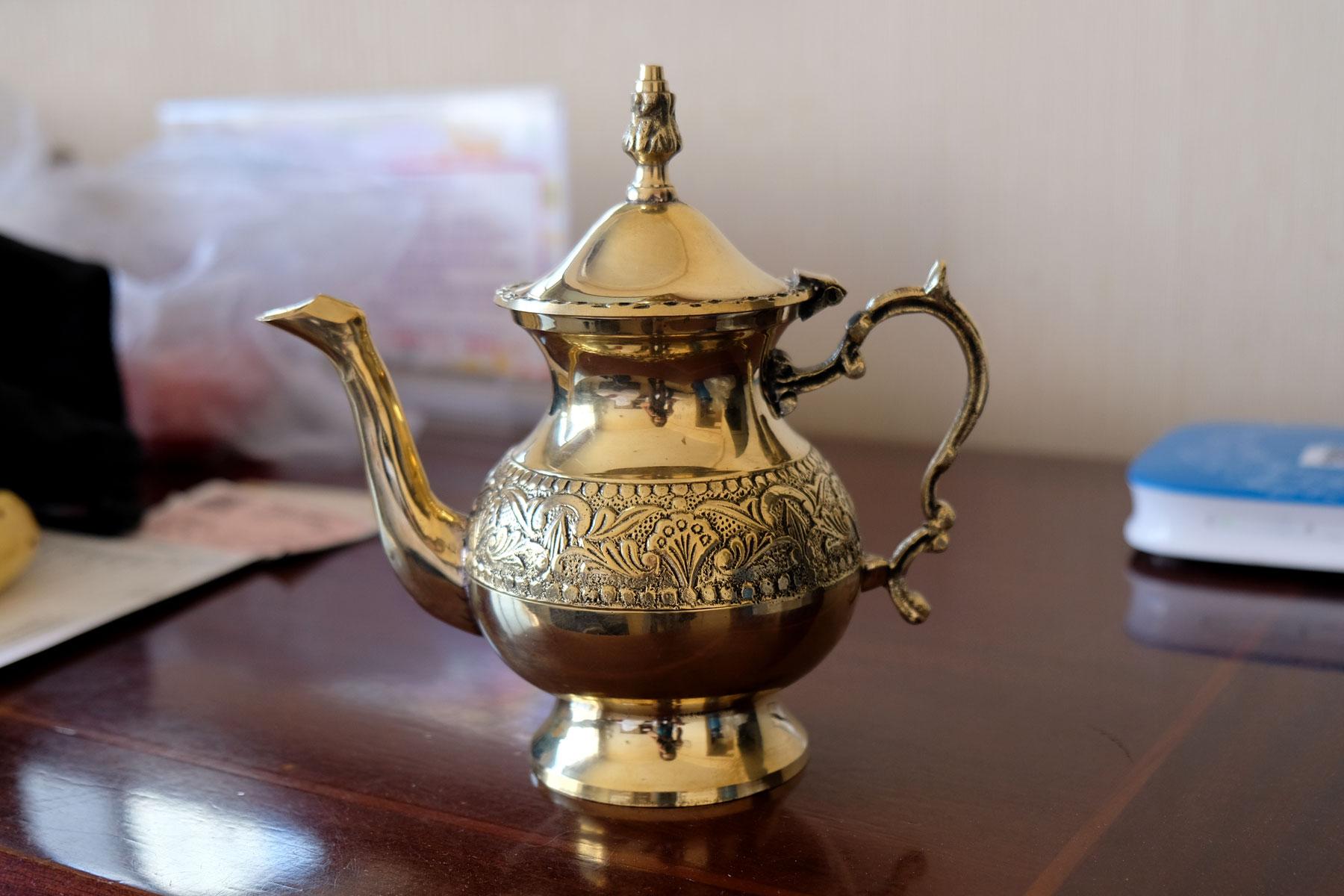 Eine goldene Teekanne.