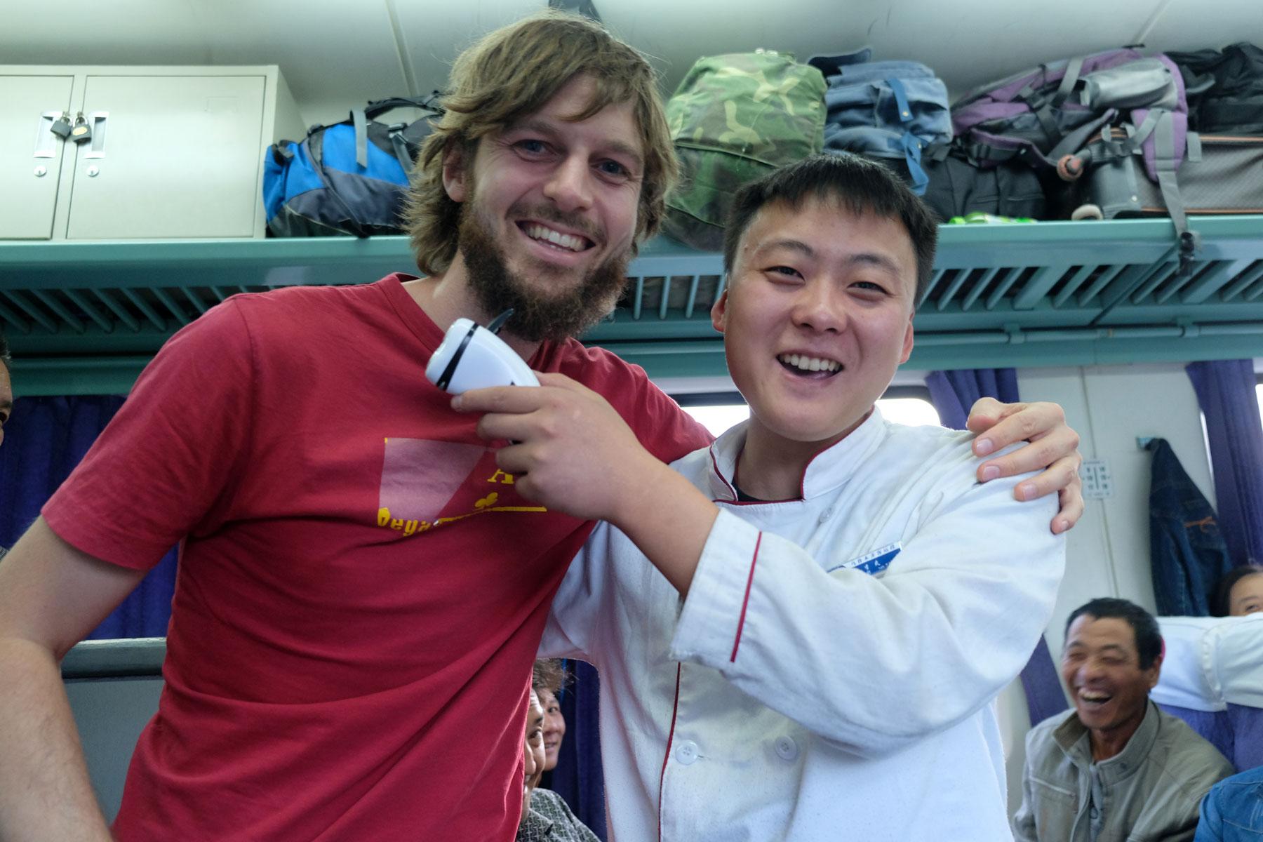 Sebastian steht neben einem chinesischen Verkäufer, der ihm einen Bartschneider an den Bart hält.
