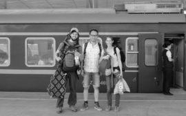 Sebastian und Leo stehen neben einem Chinesen vor einem Zug im Bahnhof von Hotan.