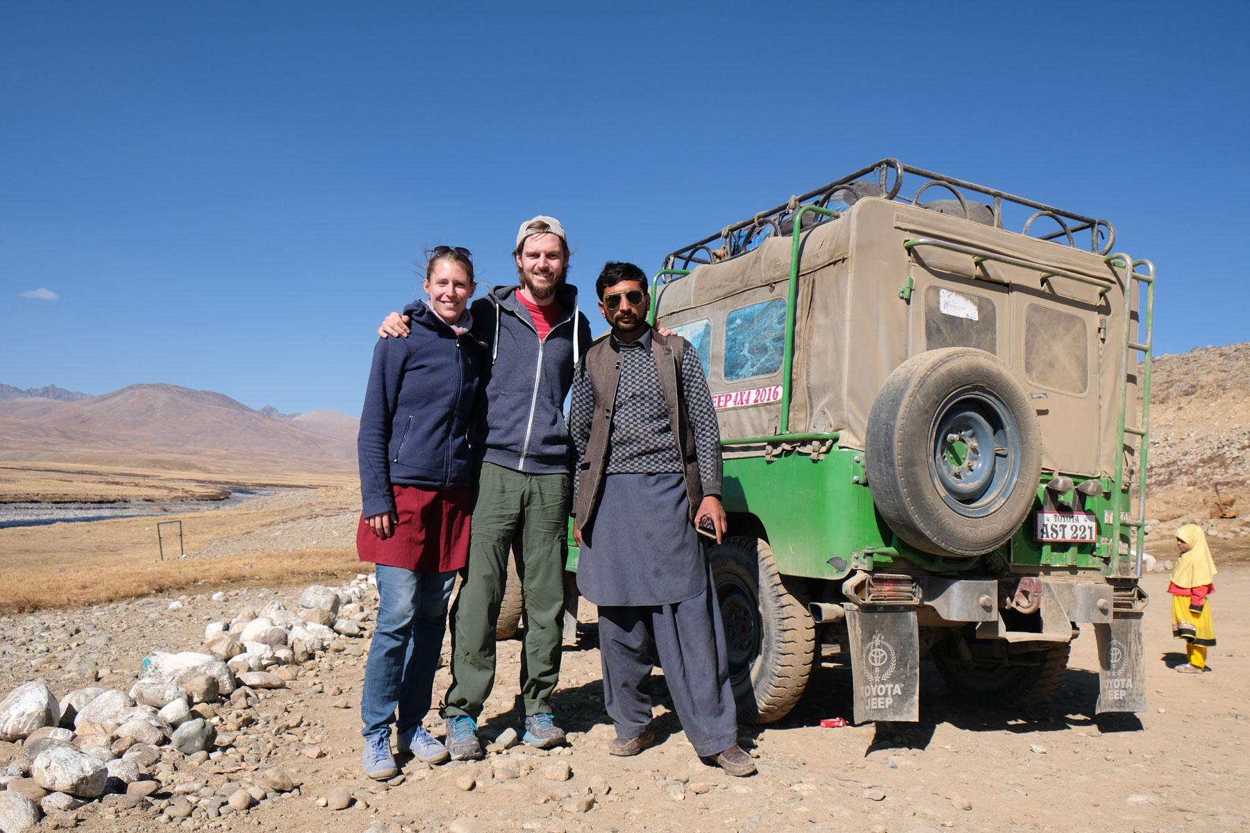 Leo und Sebastian neben einem Pakistaner und einem Geländewagen.