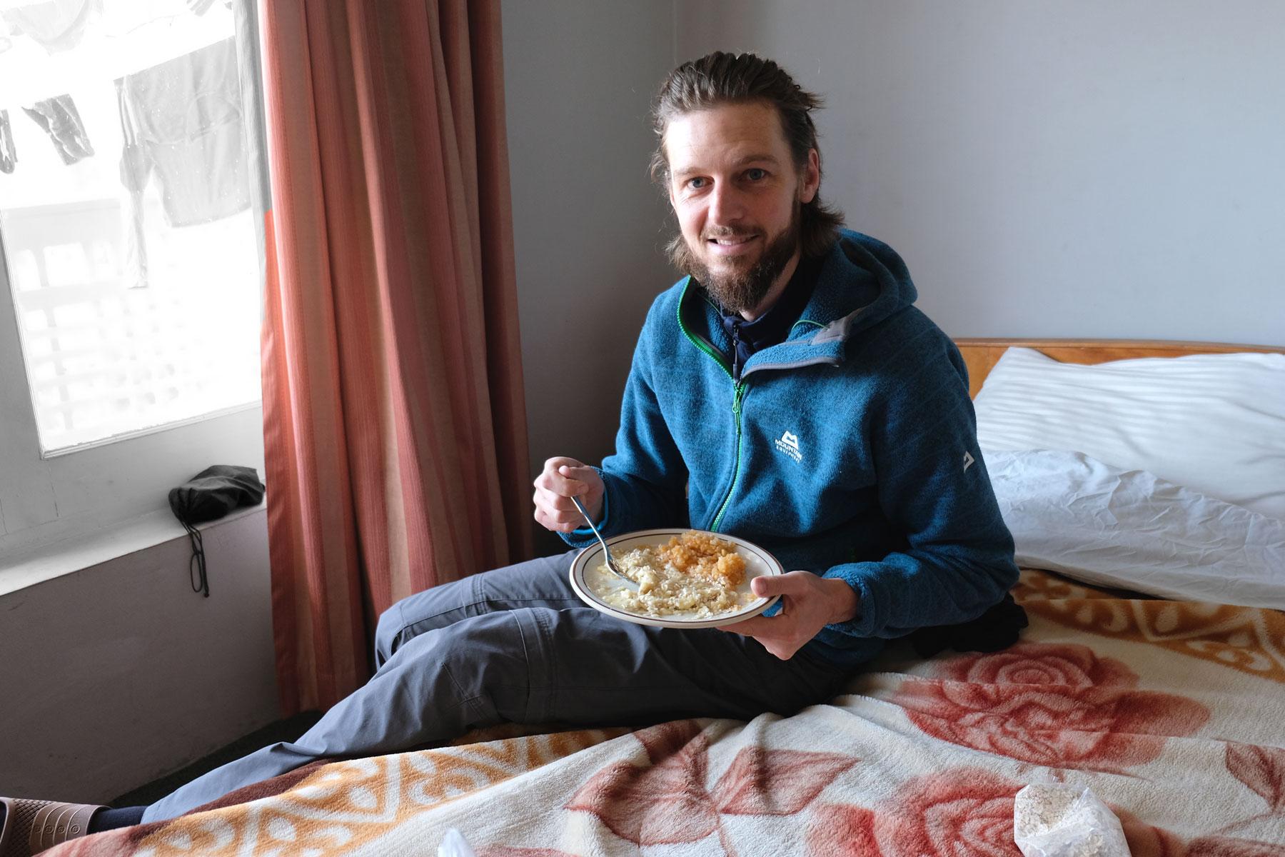 Sebastian sitzt auf einem Bett und hält einen Teller mit einem Brei aus Äpfeln und Bananen in der Hand.