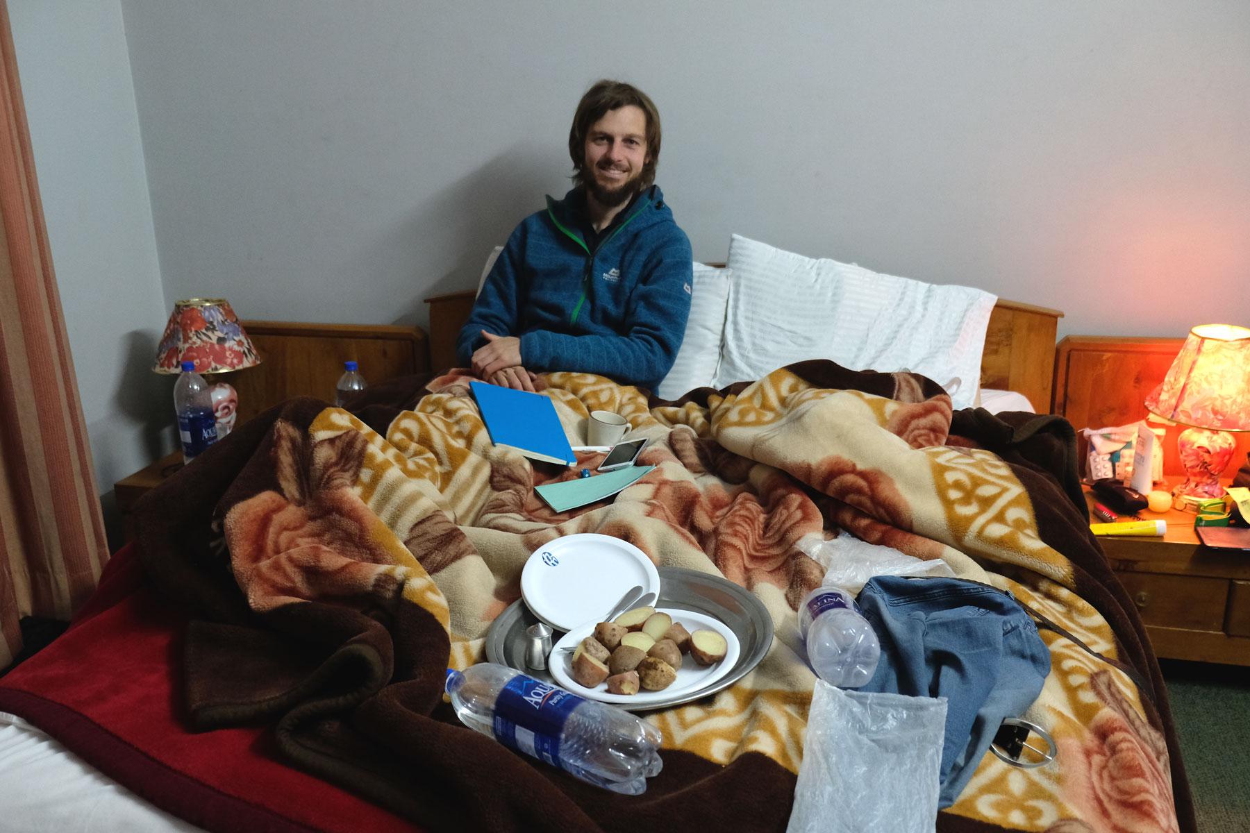 Sebastian sitzt in einem Bett, auf dem Wasserflaschen, ein Buch und ein Teller Kartoffeln liegen.