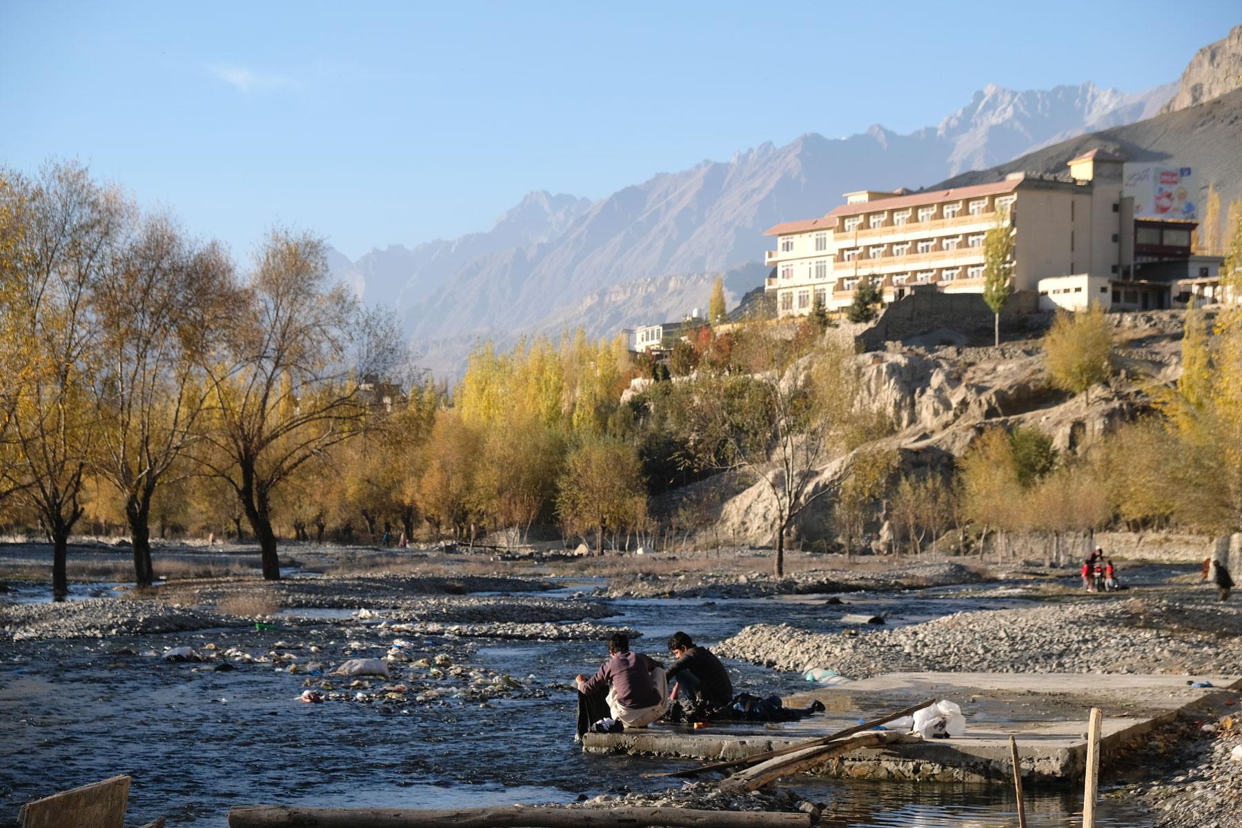 Zwei Jungen waschen in einem Fluss Wäsche. Ein Hotel in Skardu steht auf einem Felsen.