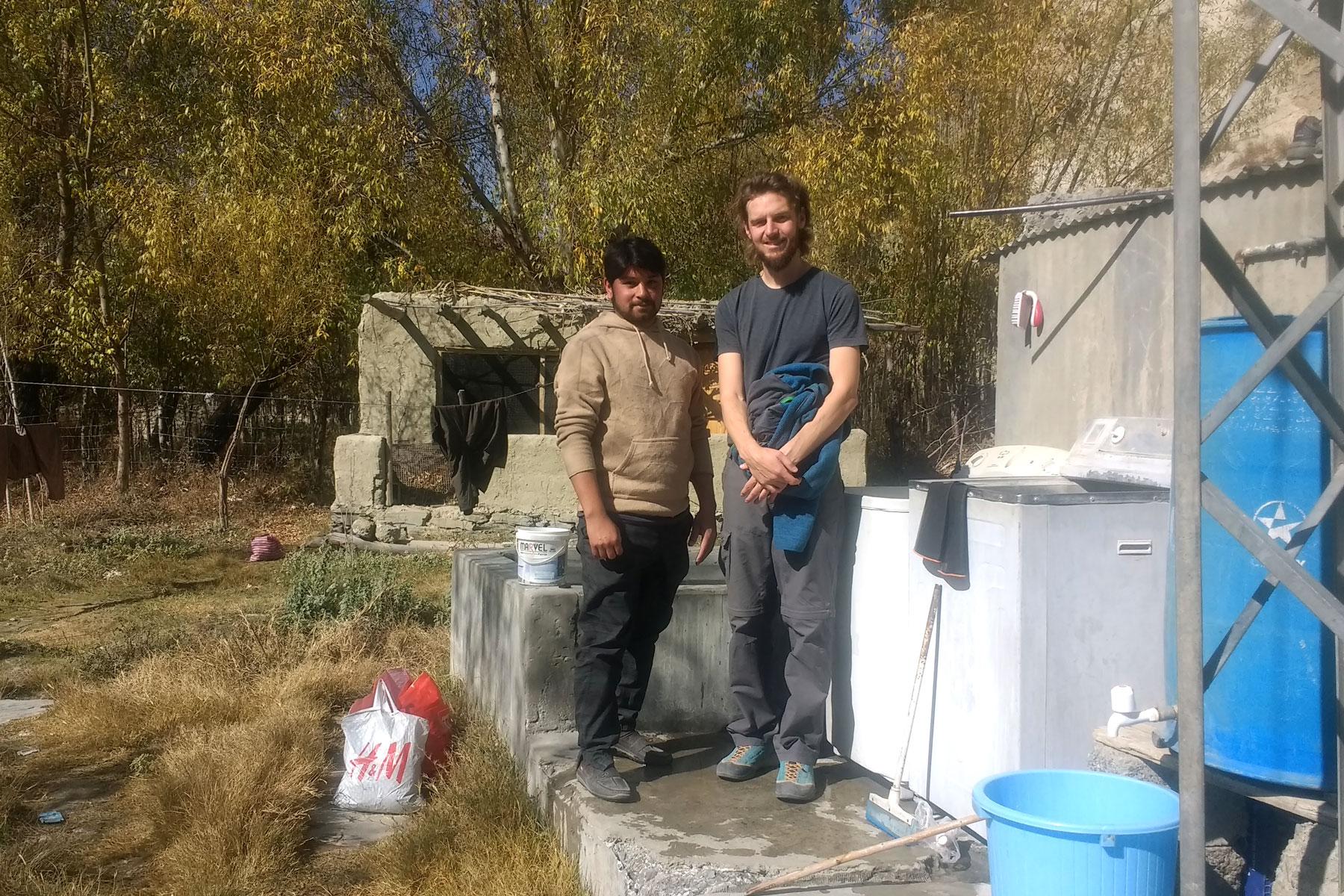 Sebastian und ein Pakistaner stehen neben einer Waschmaschine.