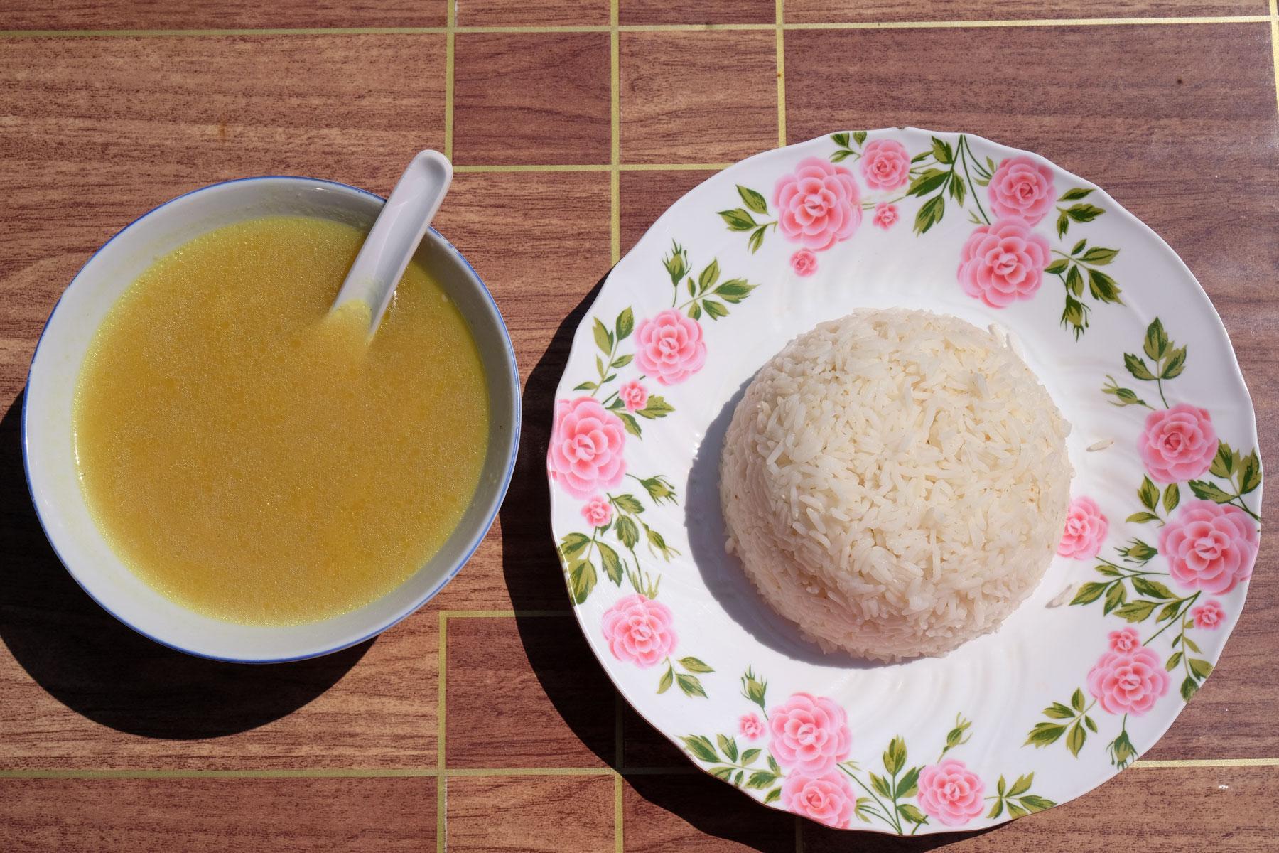 Kürbissuppe und Reis auf einem Teller.