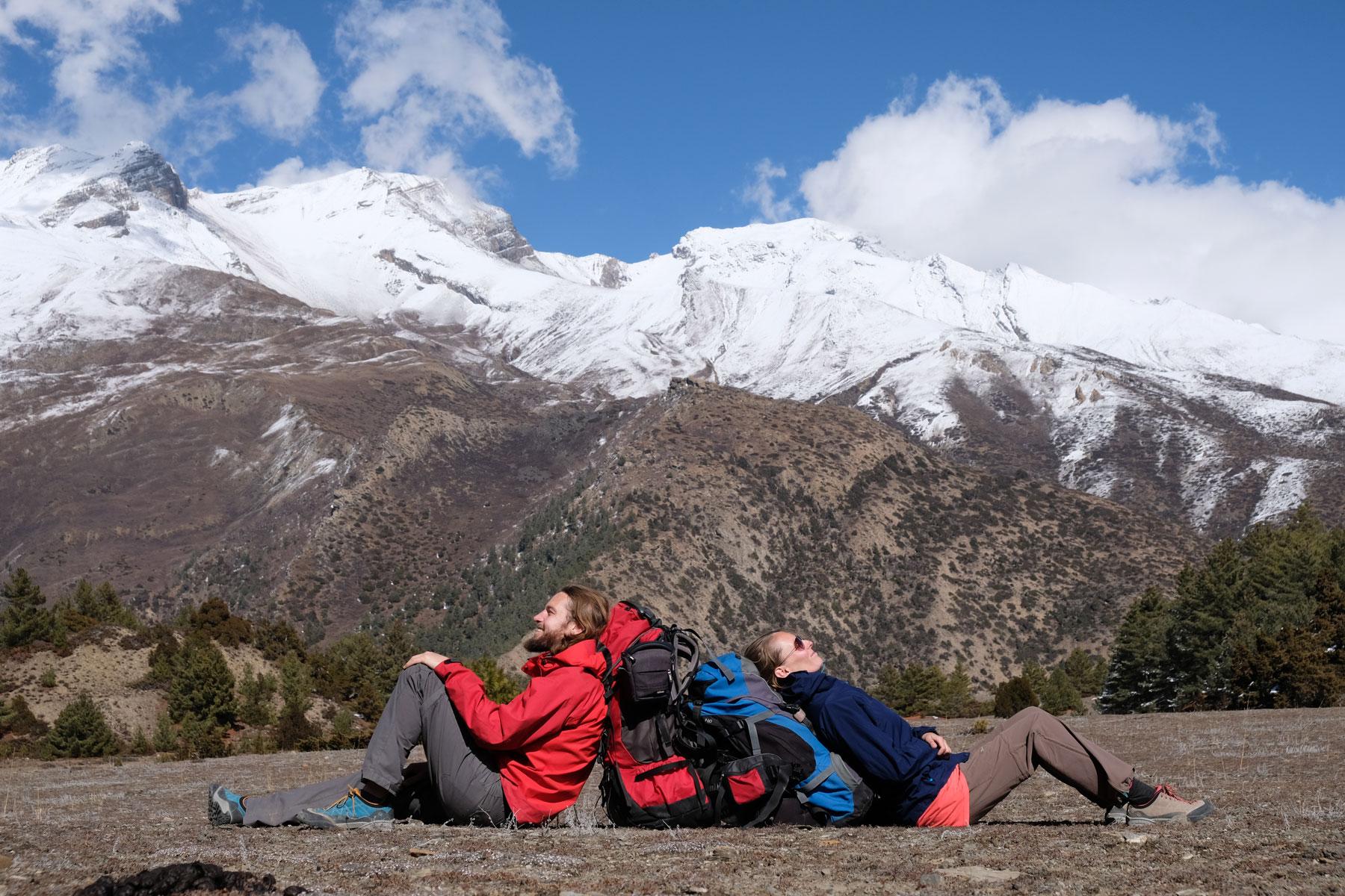 Sebastian und Leo sitzen an ihre Rucksäcke gelehnt vor einem schneebedeckten Berg im Himalaya.