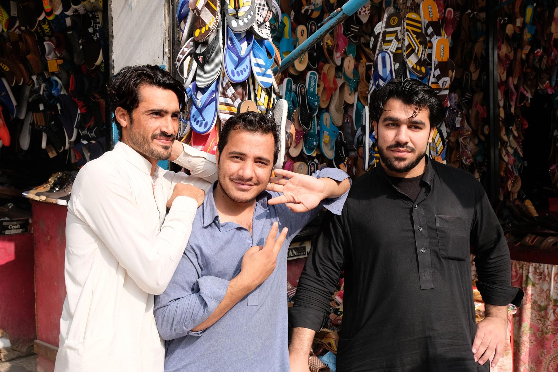 Drei Männer vor einem Geschäft für Fliflops in Rawalpindi.